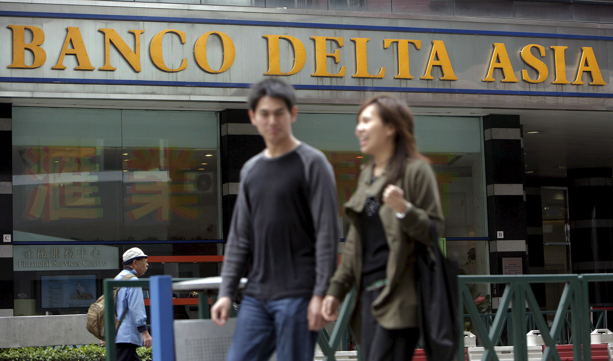 People walk past a branch of Banco Delta Asia in Macau ,China , Wednesday 14 March 2007. Chairman Stanley Au of Banco Delta Asia SARL , on Friday 16 March 2007, denied wrongdoing over frozen North Korean assets and said the bank has complied with Macau law. China on Thursday criticized a US decision to ban all transactions with the Macau bank linked to illicit North Korean funds.