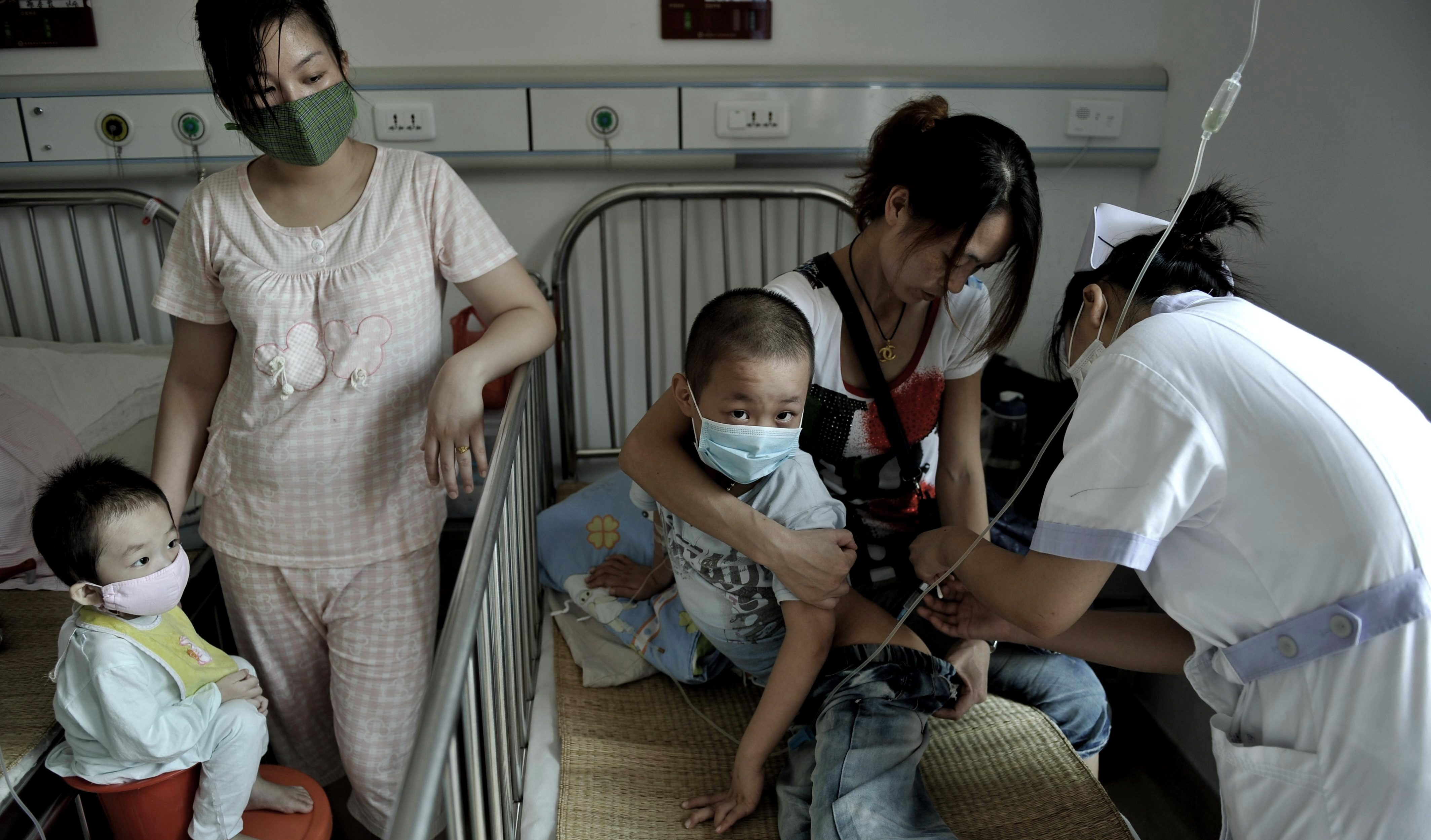 A nurse takes care of a leukemia patient in a bed in a hospital in Fuzhou in southeast China's Fujian province, Aug. 18, 2011.