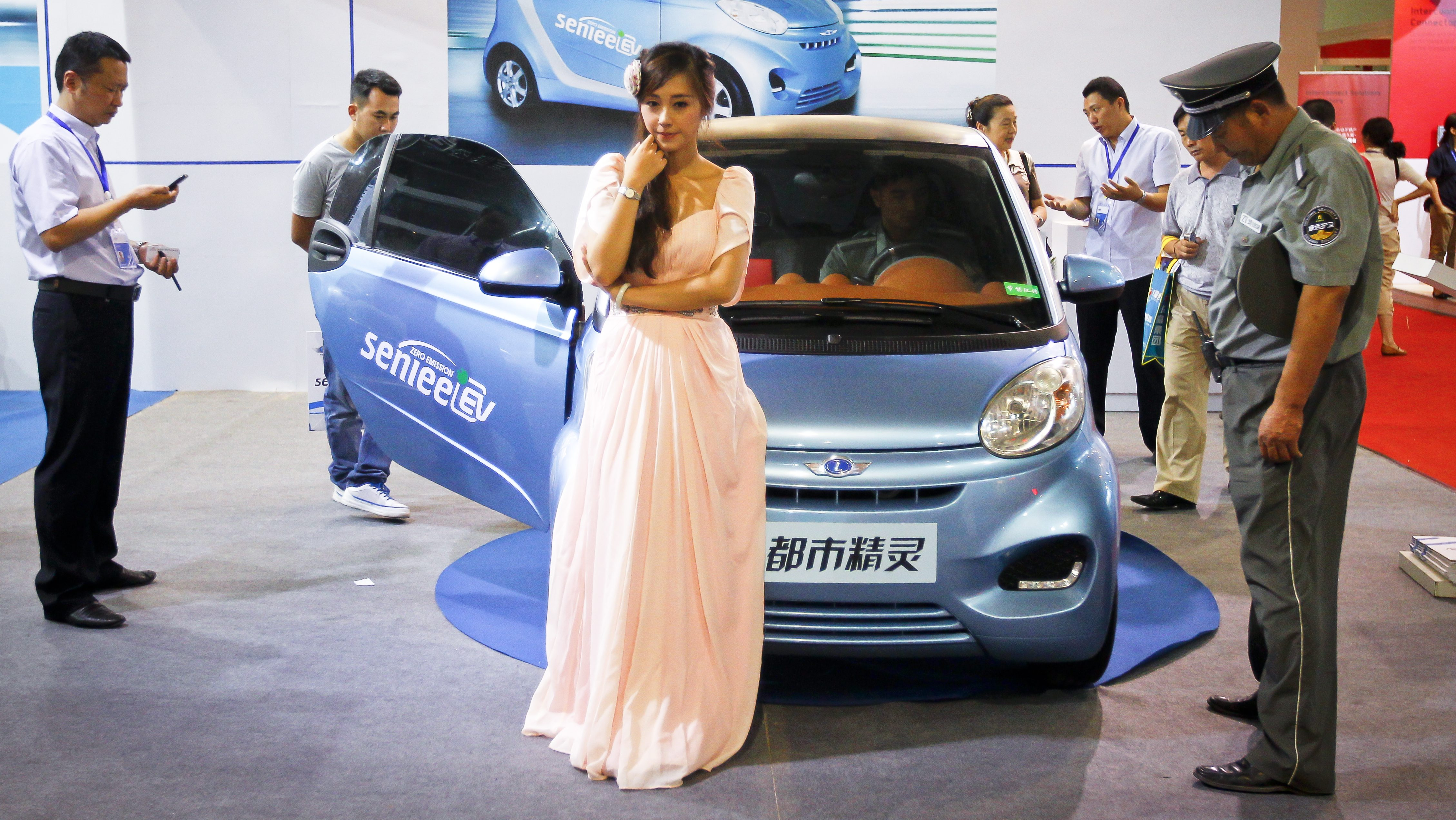 epa03294095 A model stands next to a Chinese made Senlee electric vehicle at the 8th Beijing International Pure Electric Vehicles, Hybrid Electric Vehicles and Charging Station Exhibition in Beijing, China 03 July 2012. The expo opened on 03 July and will run until 05 July. EPA/DIEGO AZUBEL