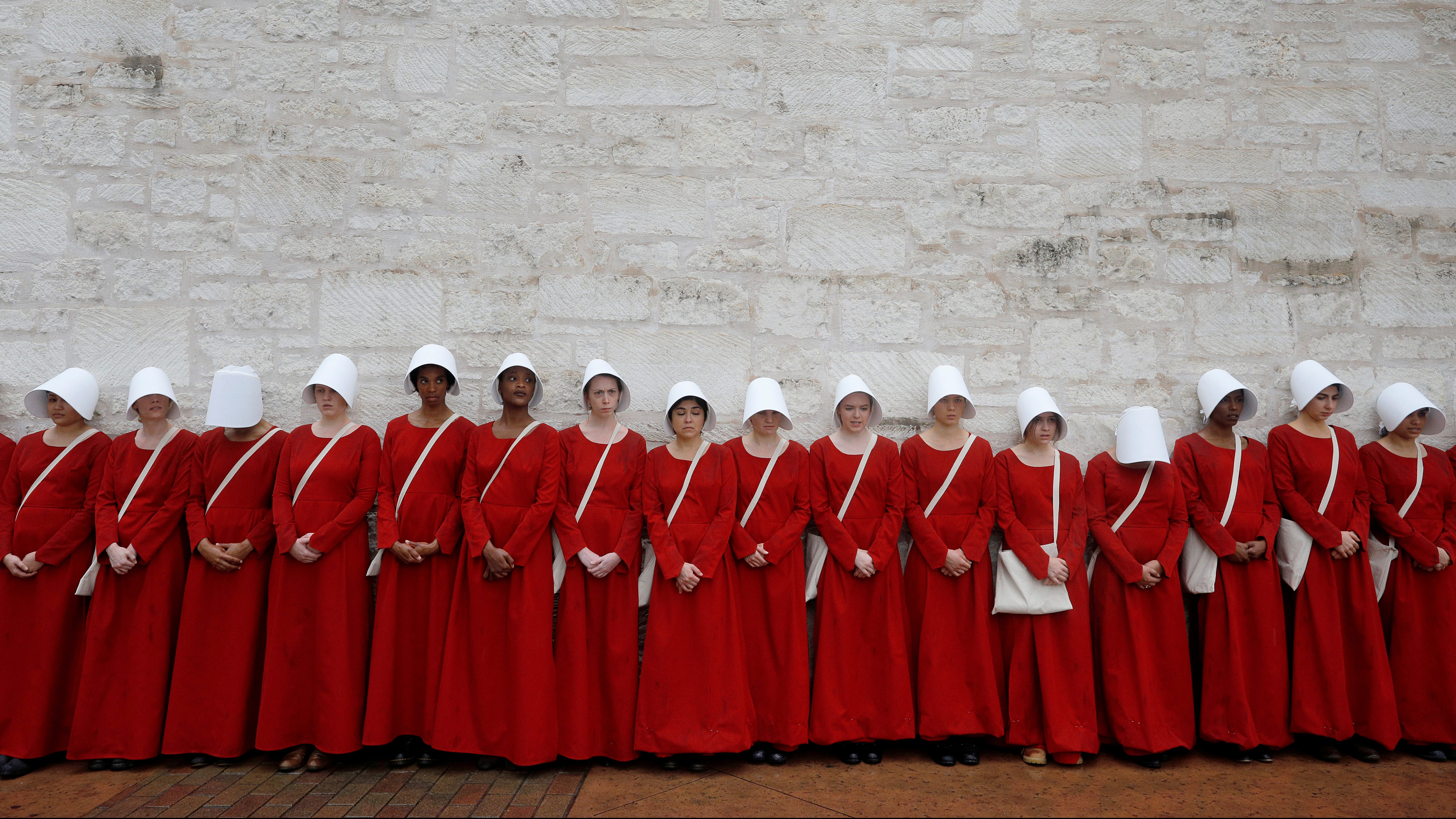 """Women dressed as handmaids promoting the Hulu original series """"The Handmaid's Tale"""" stand along a public street during the South by Southwest (SXSW) Music Film Interactive Festival 2017 in Austin, Texas, U.S., March 11, 2017. REUTERS/Brian Snyder     TPX IMAGES OF THE DAY - RTX30MMQ"""