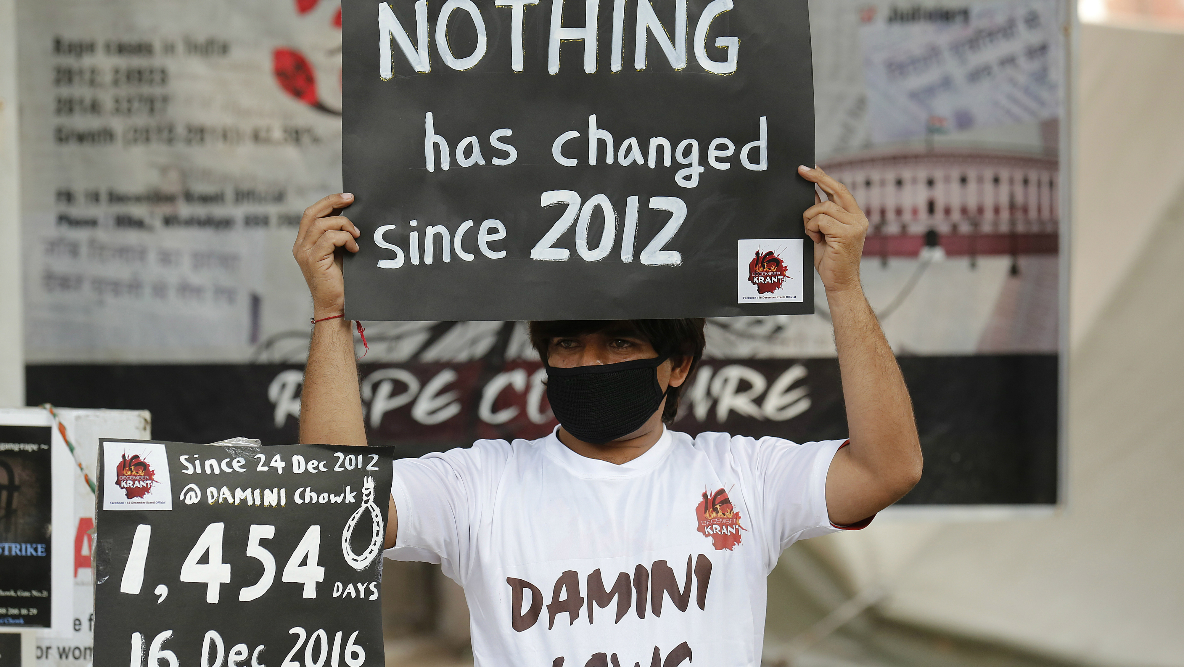 epa05678228 An Indian activist holds placards as he takes part in a protest to mark fourth anniversary of the Delhi gang rape crime, at Jantar Mantar in New Delhi, India, 16 December 2016. The protest marks the fourth year since the fatal gang rape of a 23-year-old student on a moving bus, which provoked widespread outrage and led to stricter laws against sexual assault. EPA/RAJAT GUPTA