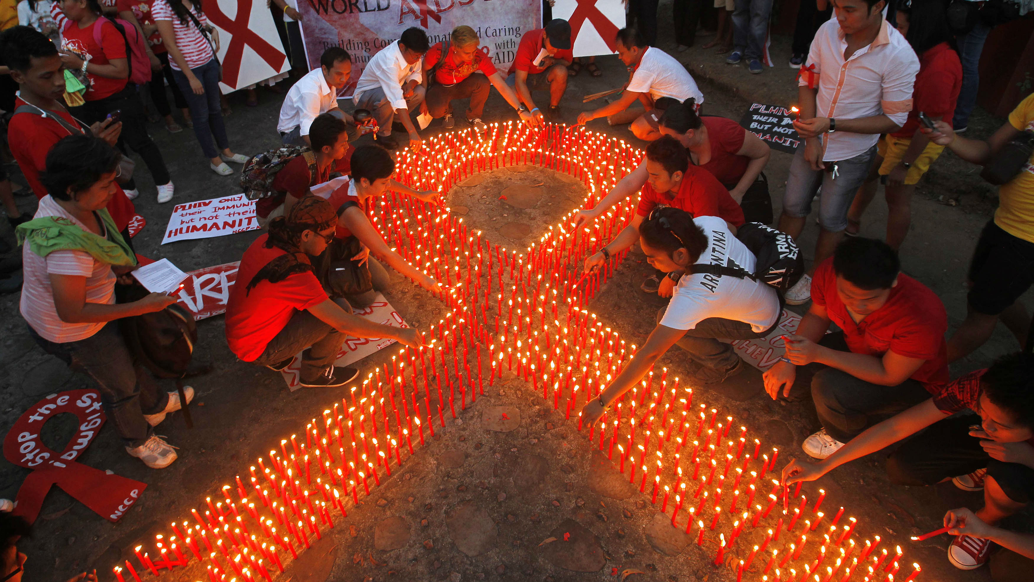 An AIDS ribbon made out of candles with people gathered around it.