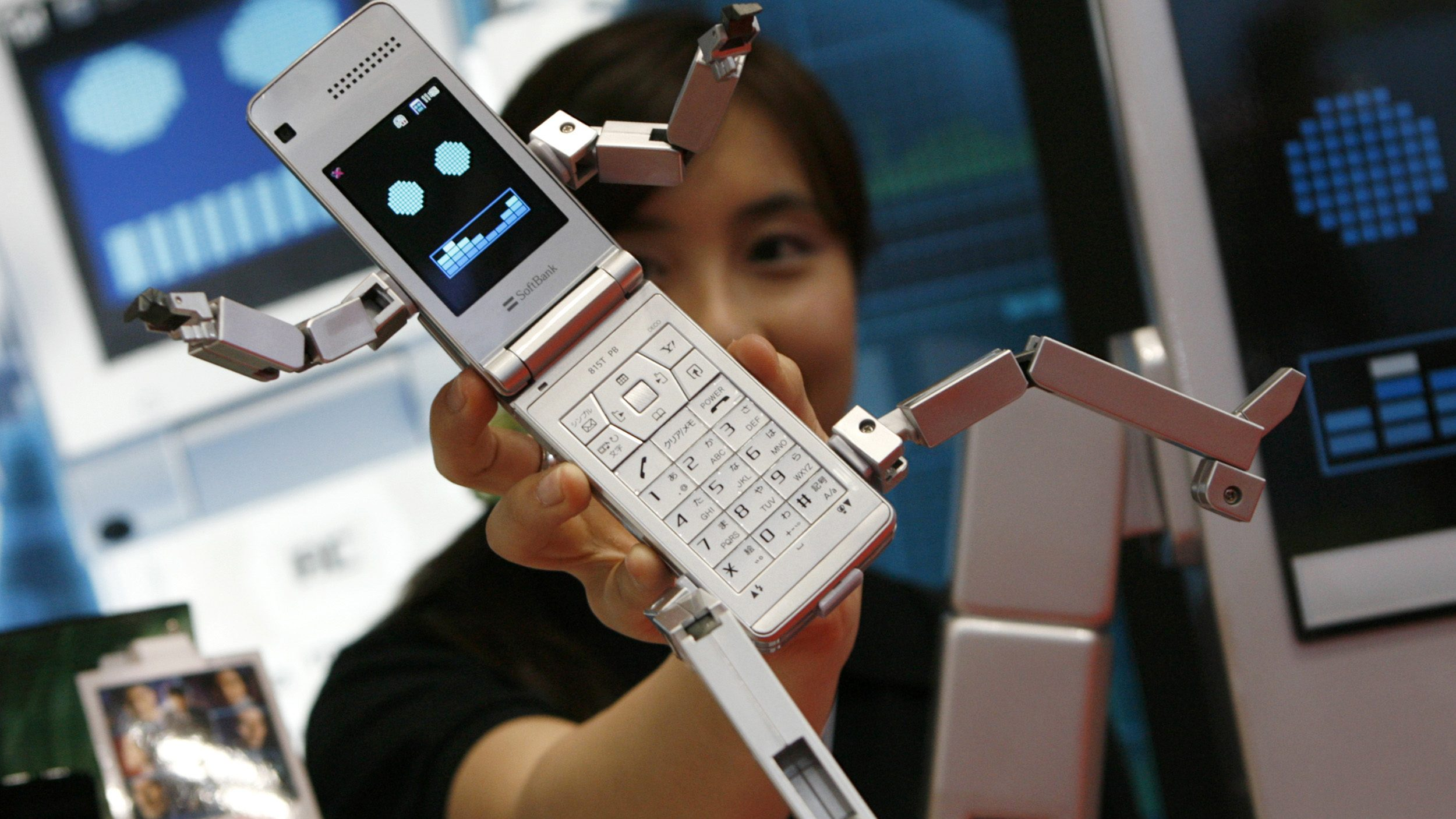 """A woman poses with the SoftBank Mobile Corp's robot-shaped mobile phone """"Phone Braver 815T PB"""" at the International Tokyo Toy Show in Tokyo June 19, 2008."""