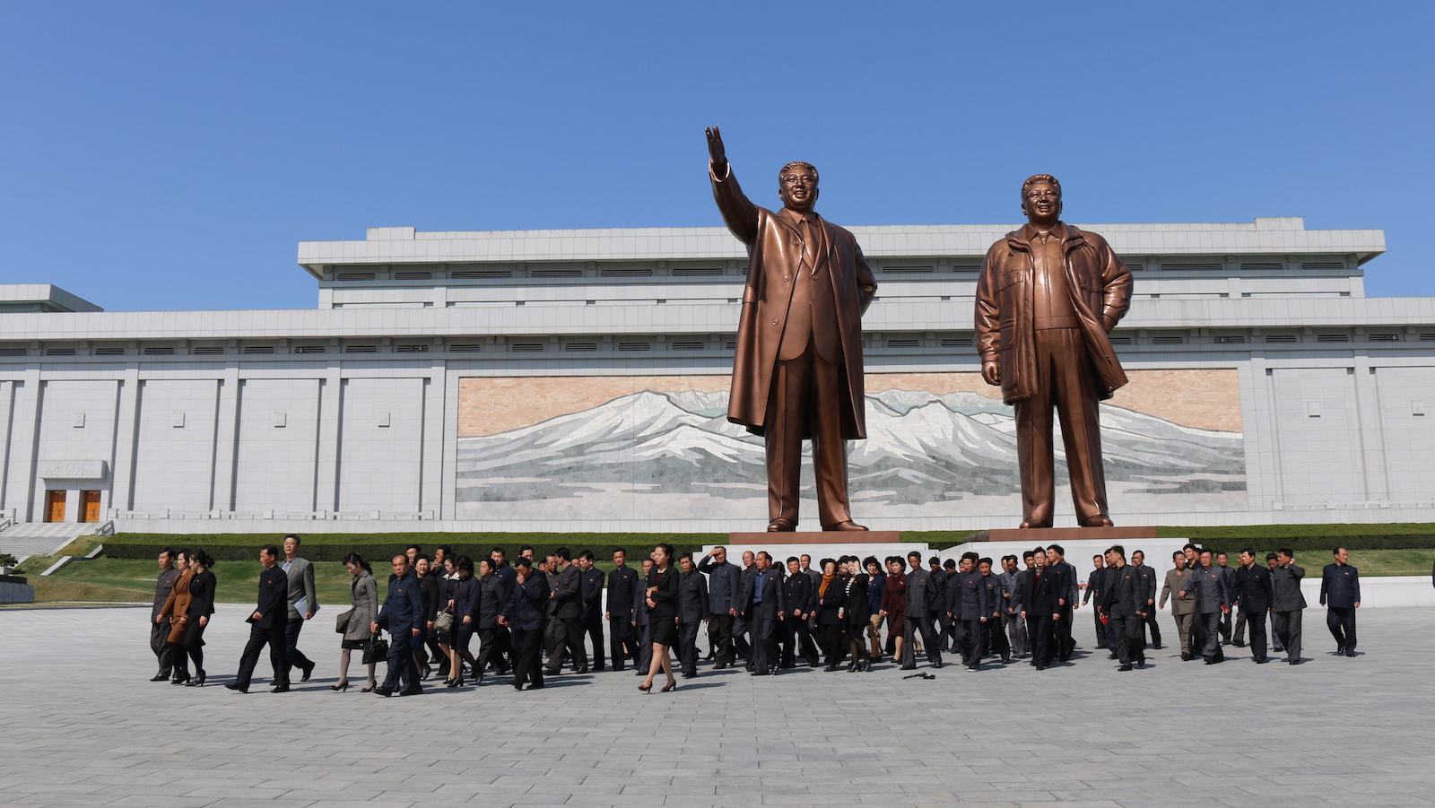 North Korea citizens under the statues of their beloved leaders
