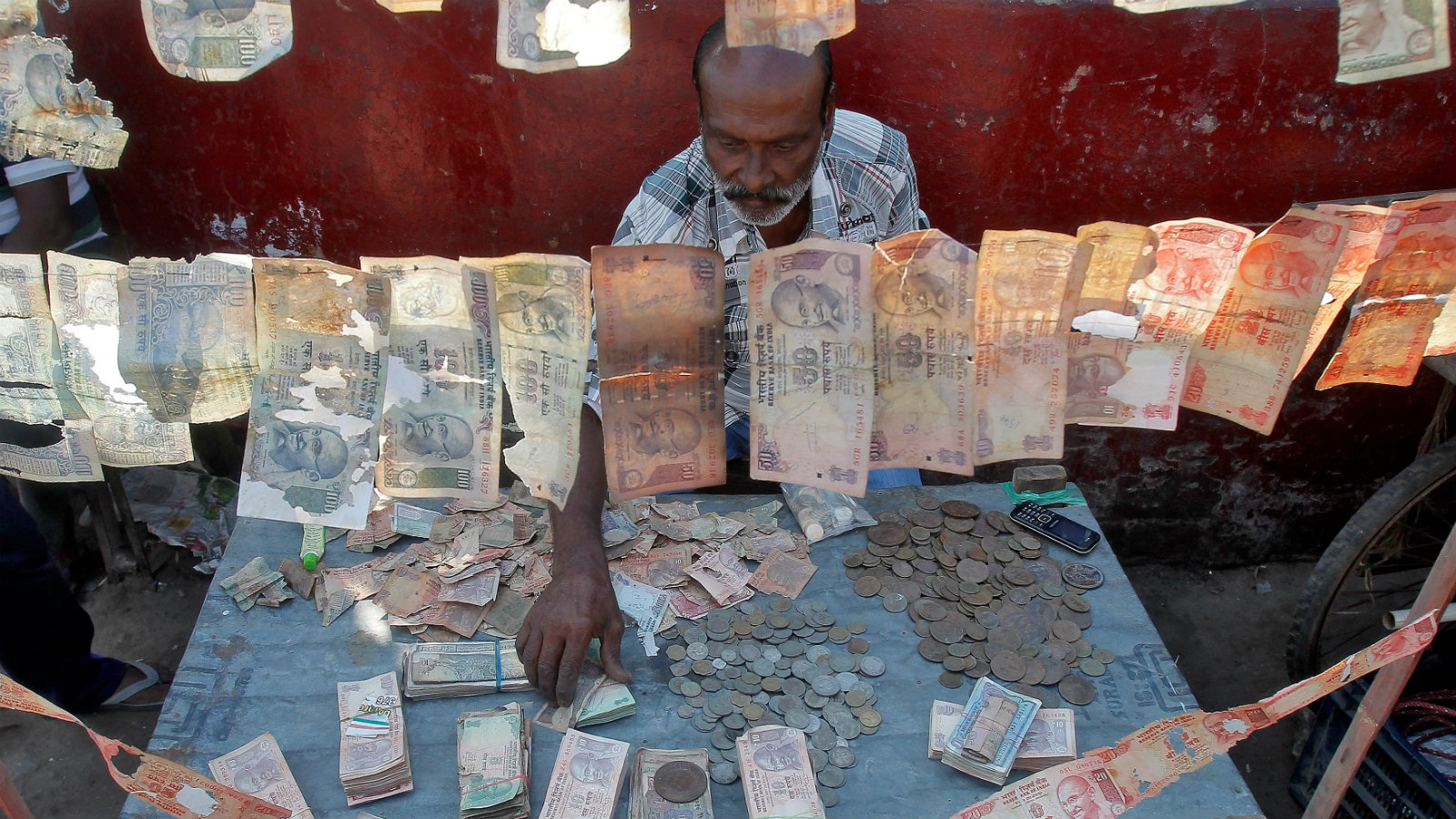 A roadside currency exchange vendor sorts Indian currency notes at his stall in Agartala, India, December 6, 2016.