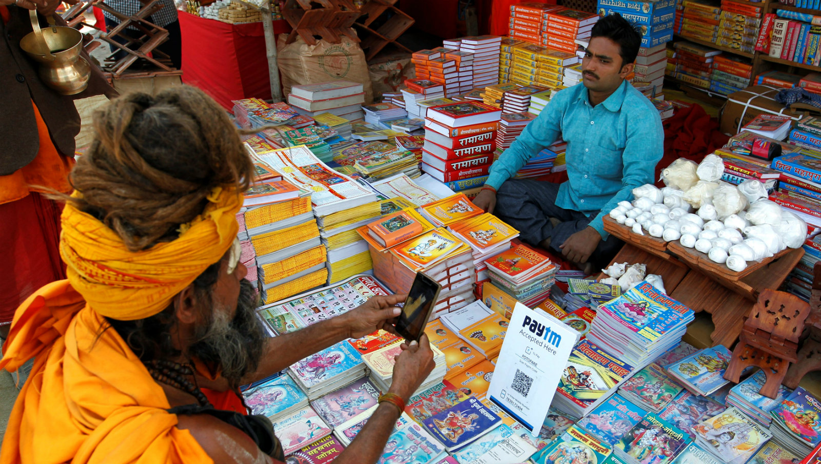 A Sadhu or a Hindu holy man pays the vendor through Paytm, a digital wallet company, after buying a book during the annual religious festival of Magh Mela in Allahabad, India, January 26, 2017. Picture taken January 26, 2017.