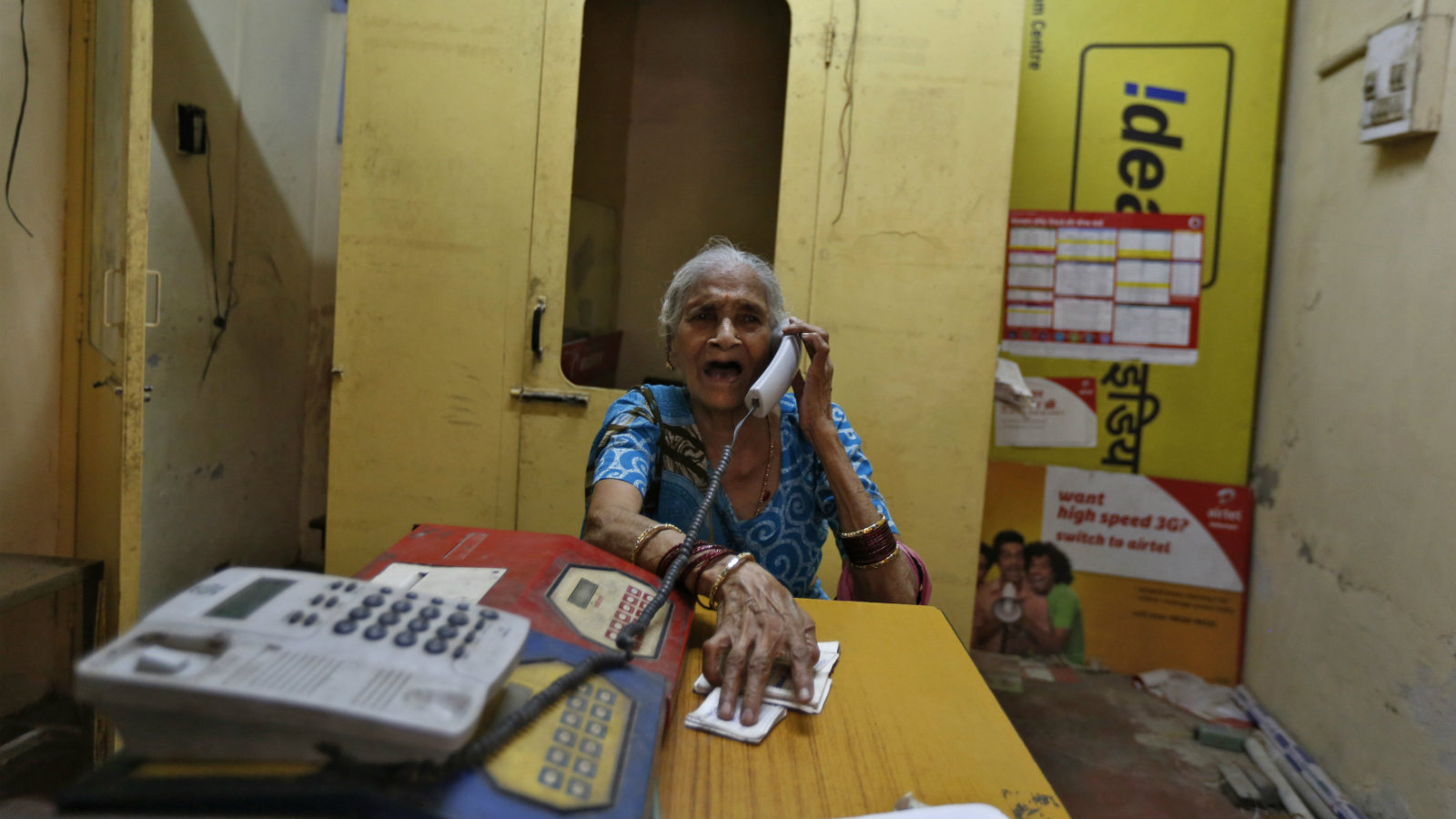 Shradeshshari Devi, 74, speaks on a phone at a local telephone booth in the old quarters of Delhi October 18, 2013.