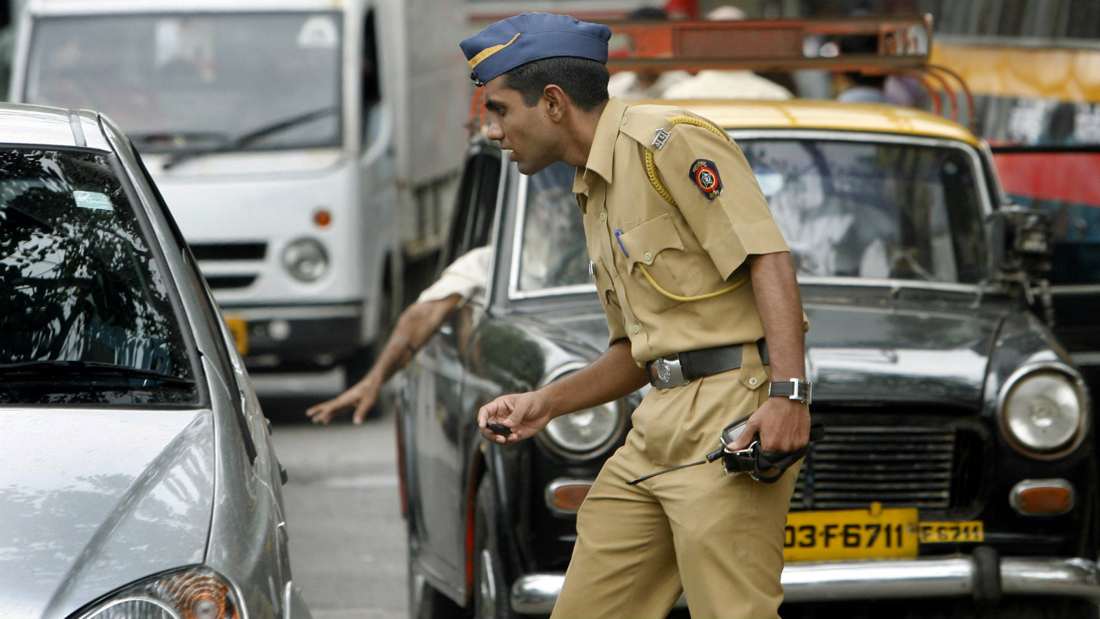 A policeman controls traffic on a busy road in Mumbai July 30, 2008. Security has been beefed up at important buildings across Mumbai after a series of bomb blasts in India's western and southern cities of Ahmedabad and Bangalore respectively last week, police said.