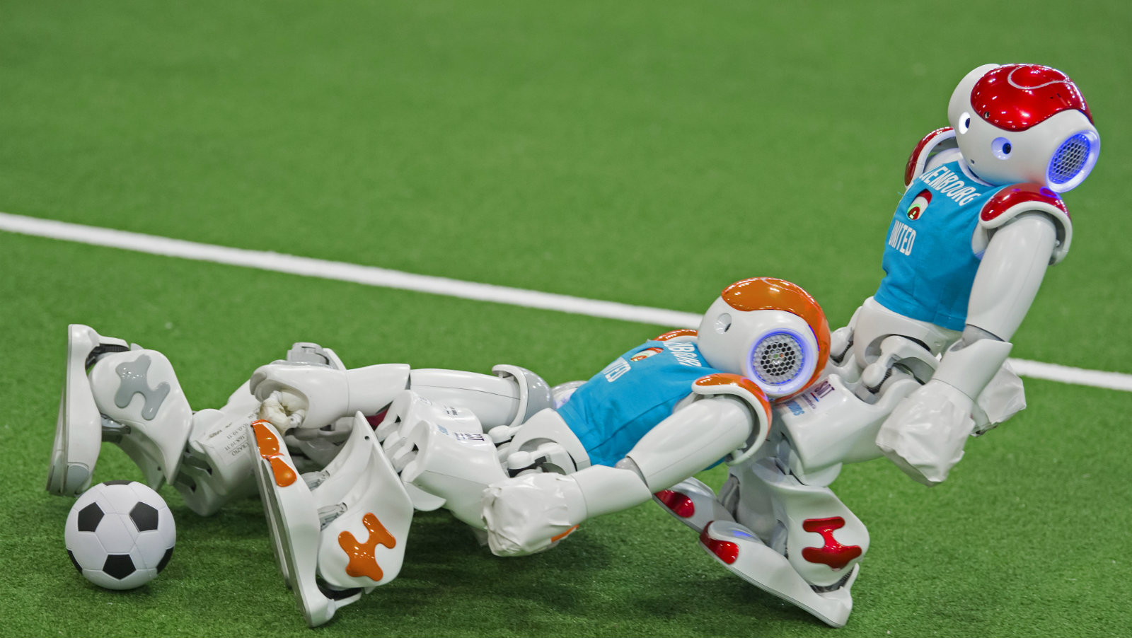 A robot of the Italian team 'nomadZ', red shirt left, challenges for the ball against robots of the Luxenbourg team, blue shirts, during a soccer match of the Standard Platform Liga competition at the RoboCup GermanOpen 2017 in Magdeburg, Germany, Sunday, May 7, 2017. Around 200 teams with more than 1,000 participants from 15 countries demonstrate the state-of-the-art in robotics with competitions such as in soccer, rescue and service robots.