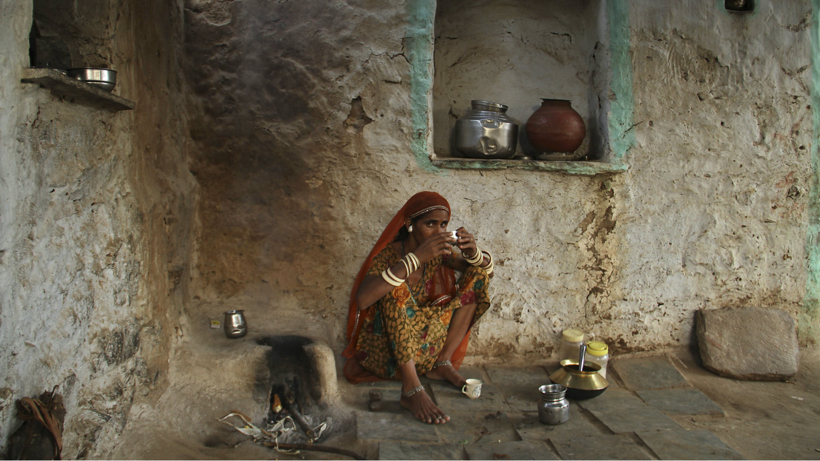 An Indian village woman sips tea sitting on the floor of her kitchen at the Ghooghra village near Ajmer, Rajasthan state, Sunday, Sept. 28, 2014.
