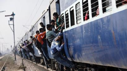 Passengers travel in an overcrowded train near a railway station at Loni town