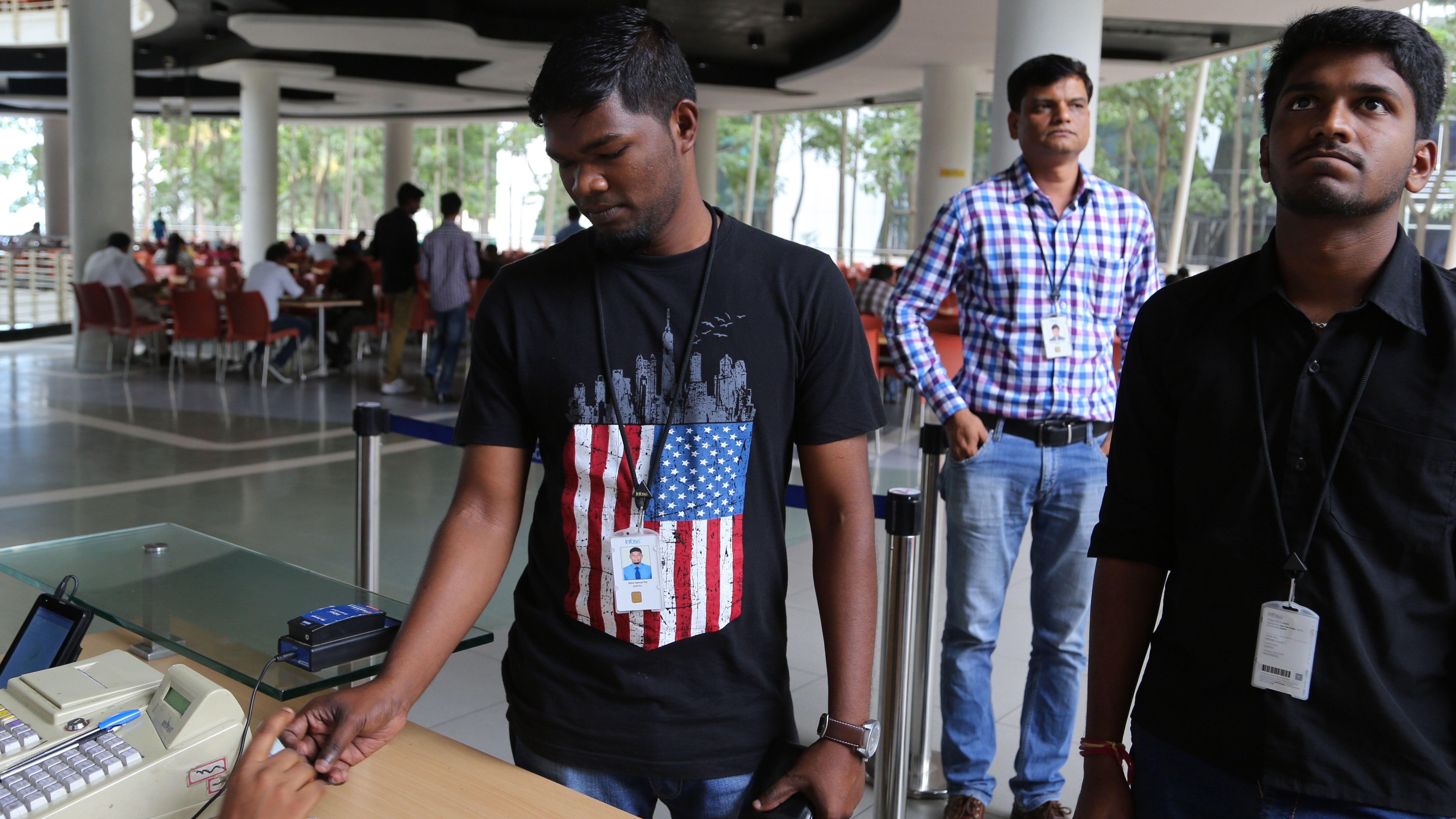 An Infosys employee sports a t-shirt featuring a U.S. flag as he buys coupons for lunch while others wait for their turn at company's headquarters in Bangalore, India, Friday, April 15, 2016. (AP Photo/Aijaz Rahi)