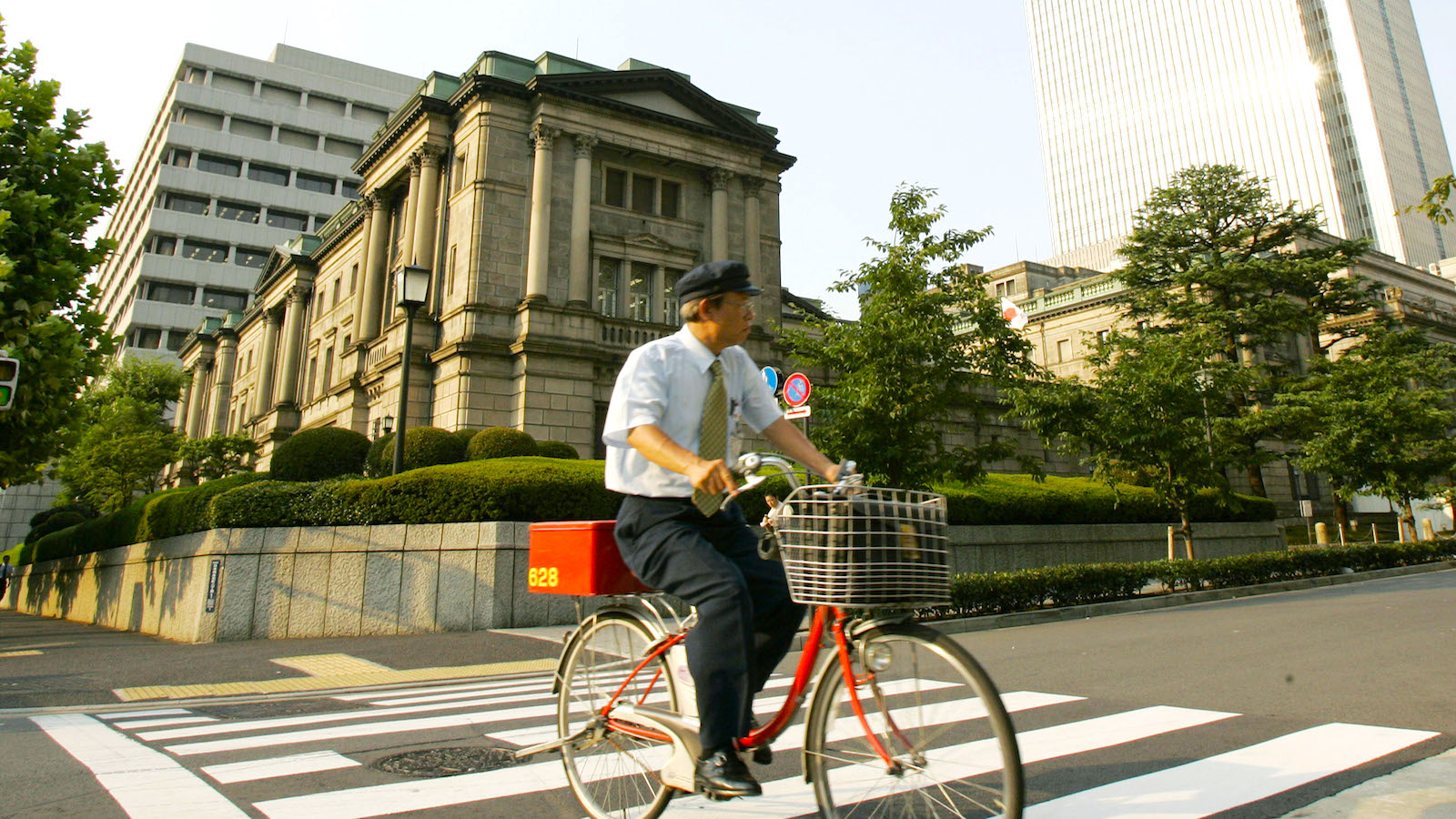 A postman rides a bicycle in front of the Bank of Japan in Tokyo Friday, Aug. 10, 2007. Japan's central bank injected 1 trillion yen (US$8.4 billion) into money markets Friday amid a Tokyo stock plunge and growing global worries about dubious U.S. mortgages. (AP Photo/Katsumi Kasahara)