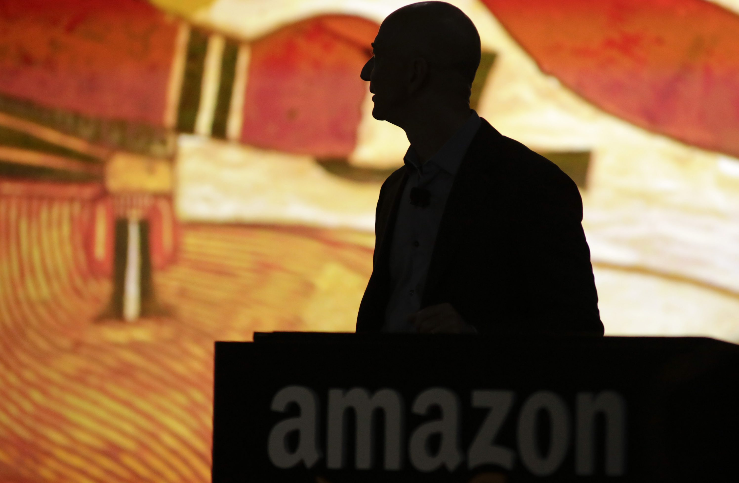 """Amazon CEO Jeff Bezos is silhouetted during a presentation of his company's new Fire smartphone at a news conference in Seattle, Washington June 18, 2014. Bezos unveiled a """"Fire""""smartphone on Wednesday equipped with a 3D-capable screen and the ability to recognize objects, music and TV shows, hoping to stand out in a crowded field dominated by Apple Inc and Samsung Electronics."""