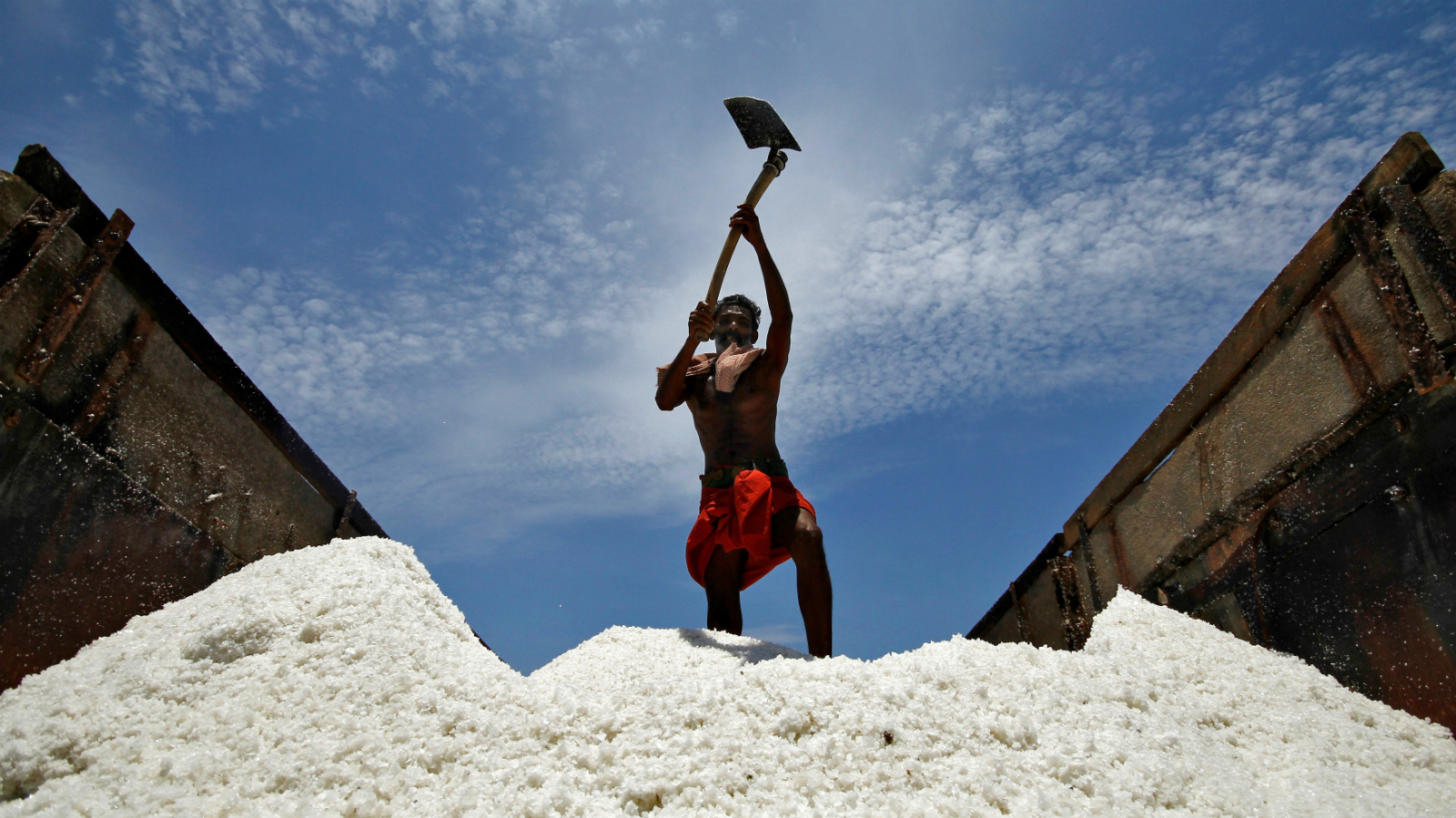 A worker loads salt onto a supply truck at a salt pan on the eve of May Day or Labour Day on the outskirts of the southern Indian city of Chennai April 30, 2014.
