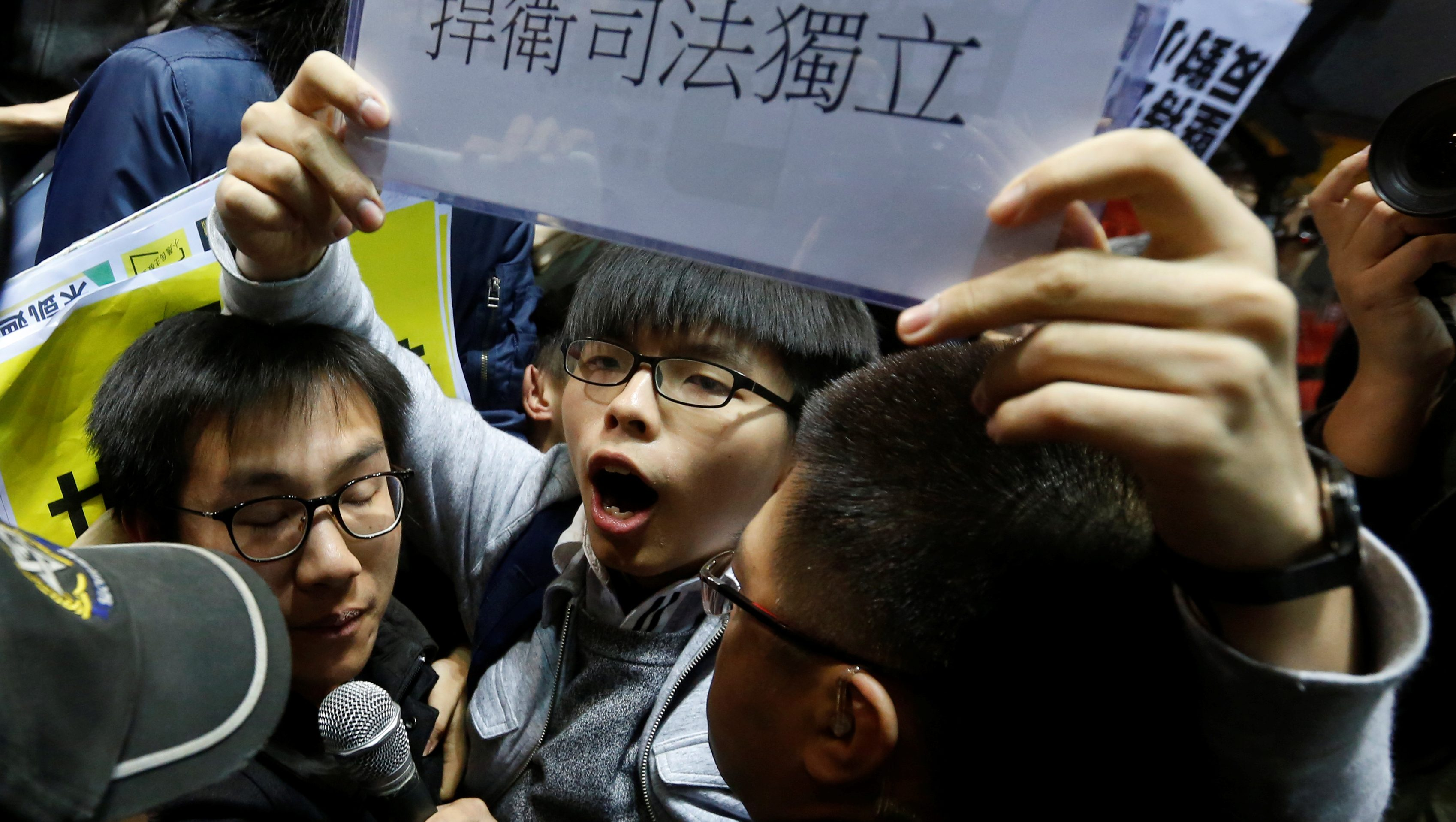 """Student leader Joshua Wong shouts and holds up a sign reading """"defend judicial independence"""" during a confrontation with security guards at a news conference held by former Chief Secretary and Chief Executive election candidate Carrie Lam in Hong Kong, China February 27, 2017. REUTERS/Bobby Yip TPX IMAGES OF THE DAY - RTS10L0D"""