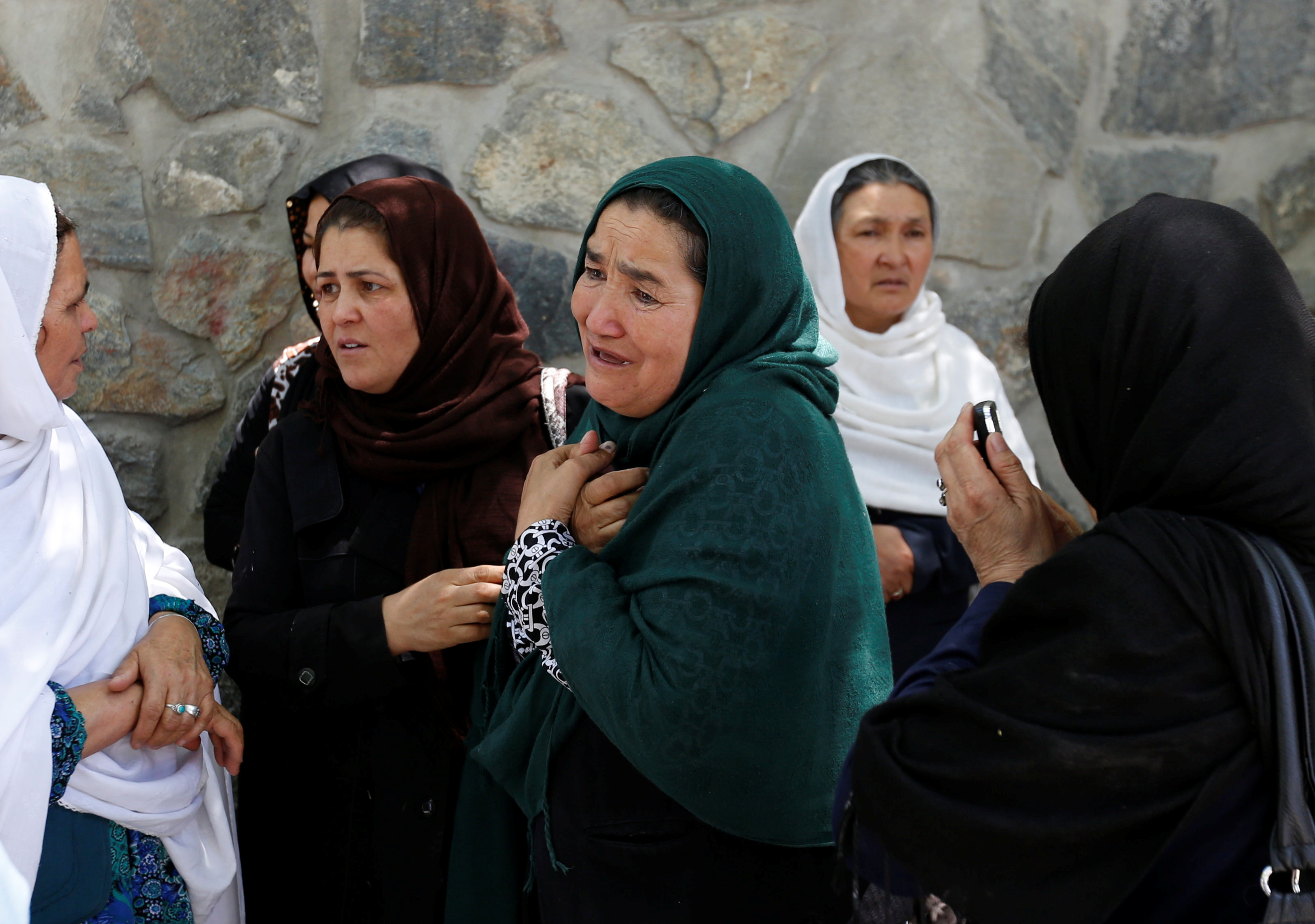 Afghan women mourn outside a hospital after a blast in Kabul, Afghanistan