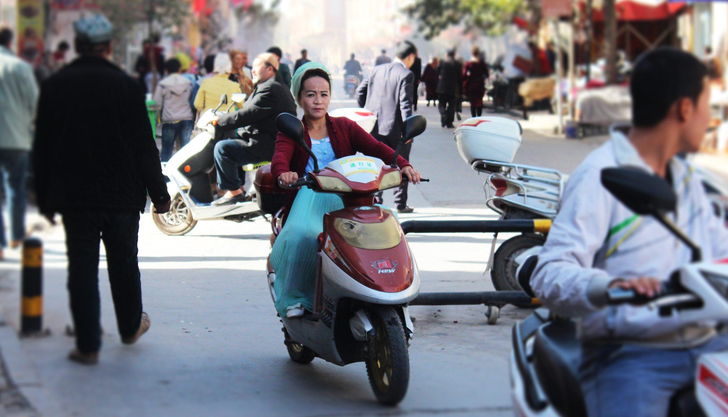 An Ughyur woman on a motorbike in Kashgar, China