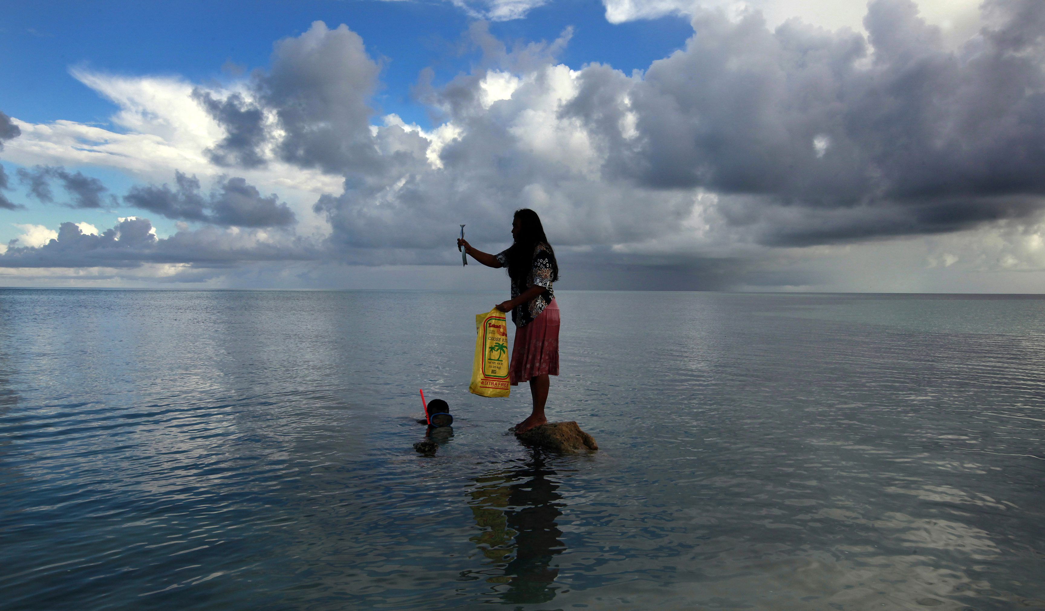 Binata Pinata stands on top of a rock holding a fish her husband Kaibakia just caught off Bikeman islet, located off South Tarawa in the central Pacific island nation of Kiribati.