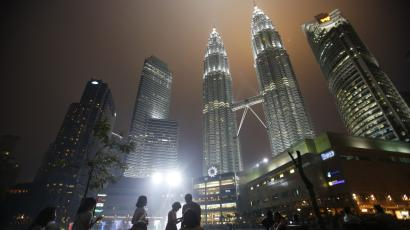 Tourists gather near the foot of the haze-covered landmark Petronas Twin Towers in Kuala Lumpur