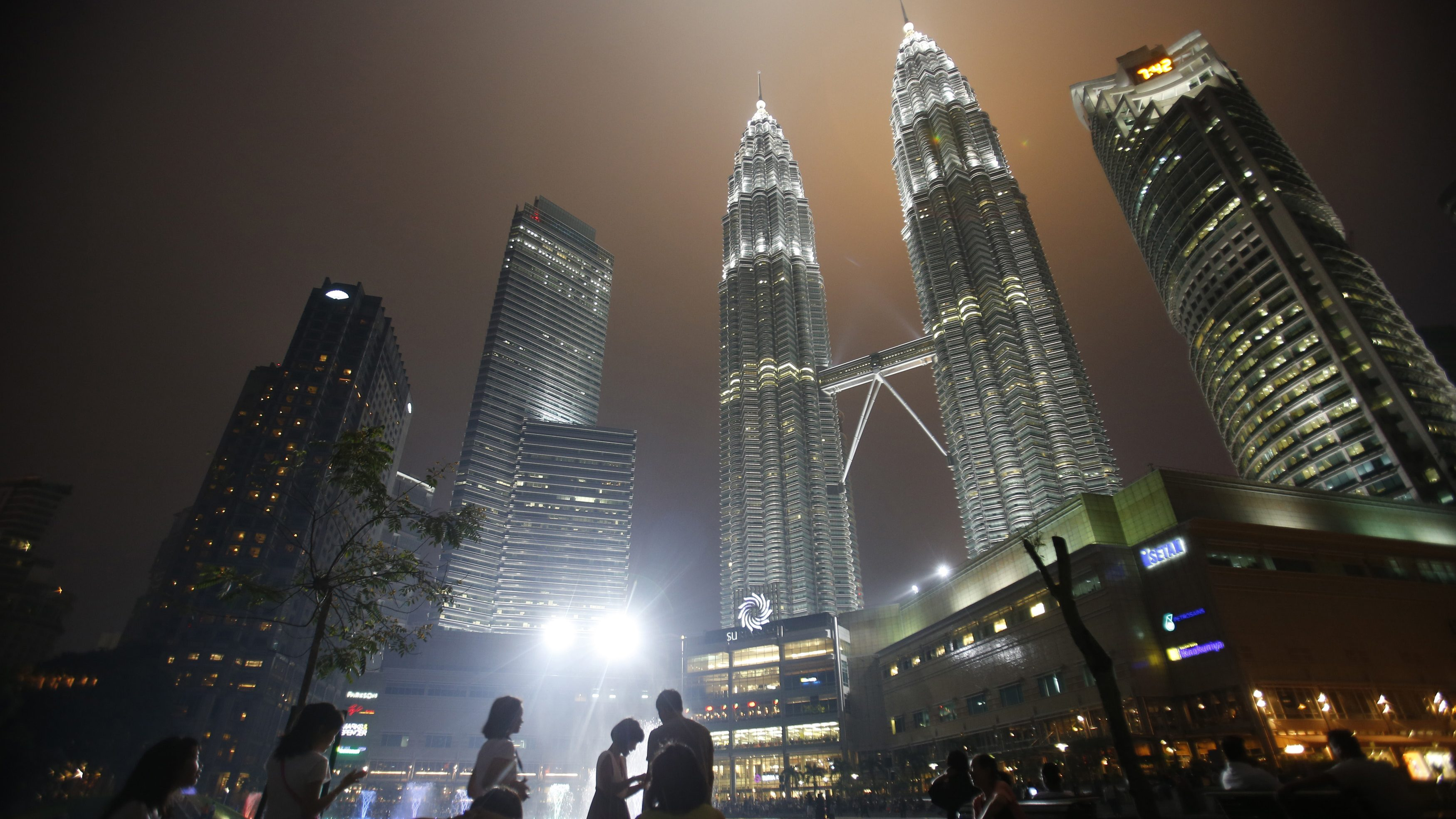 "Tourists gather near the foot of the haze-covered landmark Petronas Twin Towers in Kuala Lumpur June 25, 2013. Air quality in Singapore improved significantly to ""moderate"" pollution levels on Saturday, as Indonesian planes waterbombed raging forest fires and investigators scrambled to determine the cause of one of Southeast Asia's worst air pollution crises. In Malaysia, the haze spread north. Air quality in Kuala Lumpur, the capital, and in several surrounding areas worsened into the ""unhealthy"" zone. The air quality was now ""unhealthy"" in 17 areas of Malaysia and ""very unhealthy"" in one area."