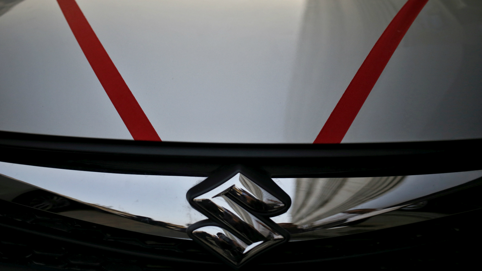 The logo of Maruti Suzuki India Limited is seen on car parked outside a showroom in New Delhi, India, February 29, 2016