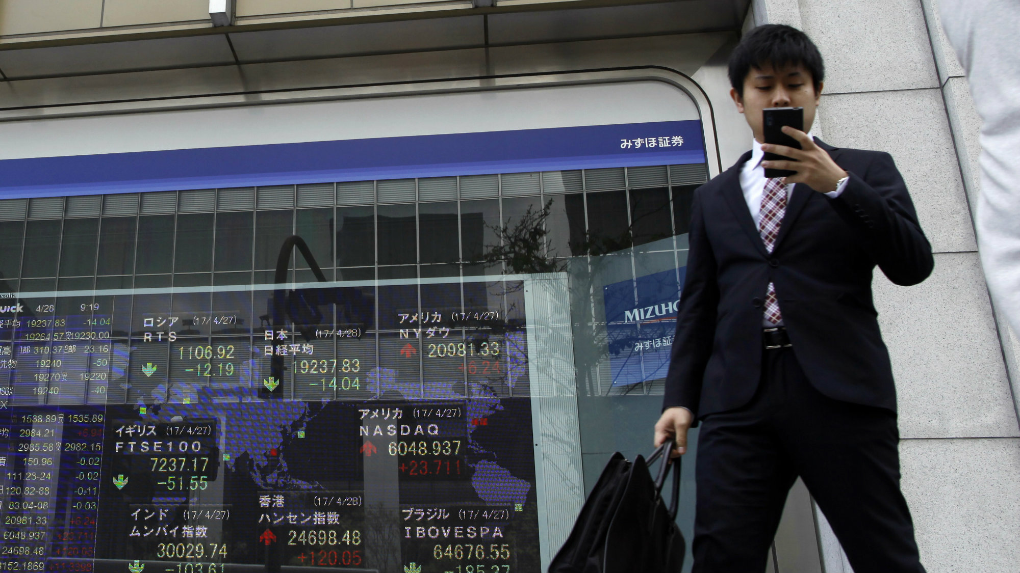 A man takes a look at a smartphone in front of an electronic stock board showing global stock index at a securities firm in Tokyo, Friday, April 28, 2017.