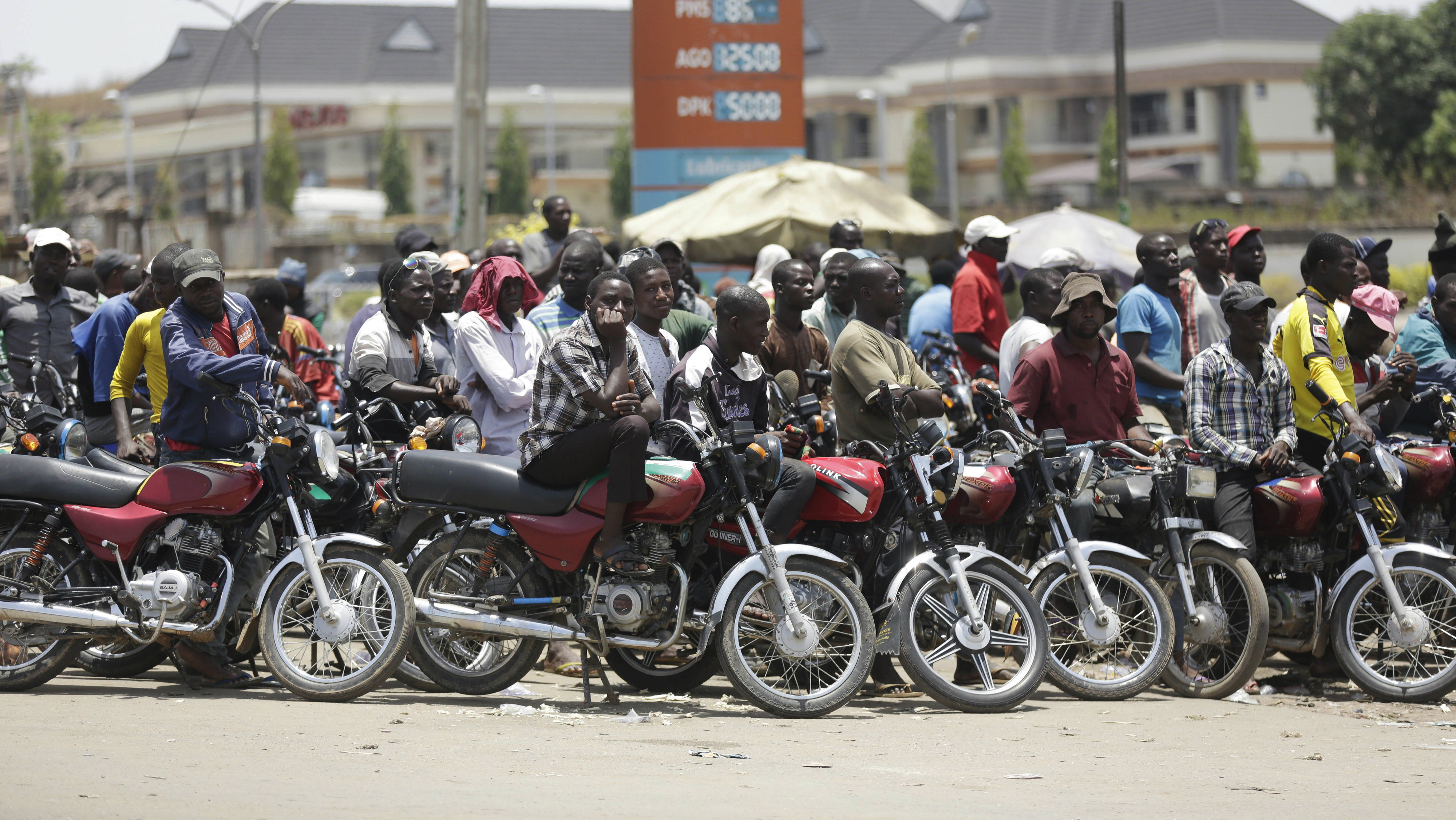 In this photo taken Sunday April 10, 2016, motorcycles wait for fuel at the petrol station in Abuja, Nigeria. Nigeria's government announced Wednesday May 11, 2016 it is lifting a controversial subsidy on gas, nearly doubling the price amid a massive fuel shortage and militant attacks on oil installations in Africa's biggest petroleum producer
