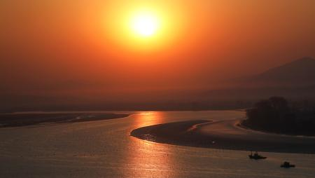 The sun rises from the North Korean side of the Yalu River near the town of Sinuiju, seen from Dandong in China's Liaoning Province, April 1, 2017. REUTERS/Damir Sagolj - RTX347T6