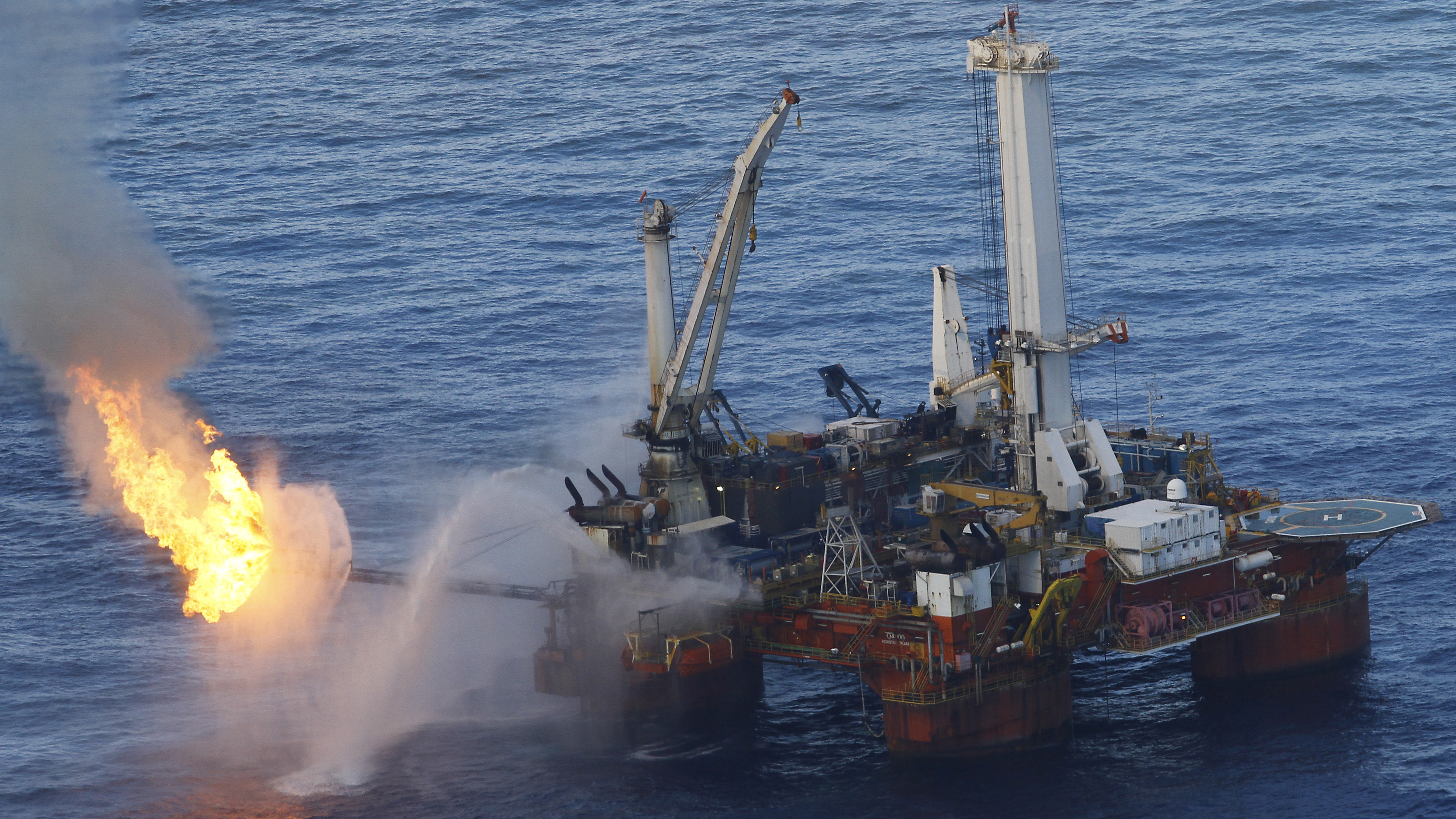 Fire and smoke rise from the Q4000 oil vessel, as drilling of two relief wells continue, in the Gulf of Mexico, July 4, 2010. A commission appointed by President Barack Obama to study the causes of the Gulf of Mexico oil spill gives academics and environmentalists a prominent role in making recommendations about the future of offshore drilling in the United States.    REUTERS/Lyle W. Ratliff (UNITED STATES - Tags: DISASTER ENERGY ENVIRONMENT BUSINESS IMAGES OF THE DAY) - RTR2G3S0