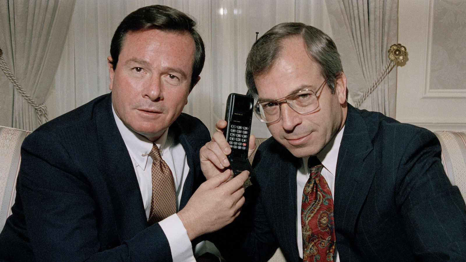 Paul Stern, left, president and CEO of Northern Telecom poses with a phone for photographers, with George Fisher, chairman of the board and CEO of Motorola, Inc. in New York, Feb. 10, 1992. (AP Photo/David Cantor)