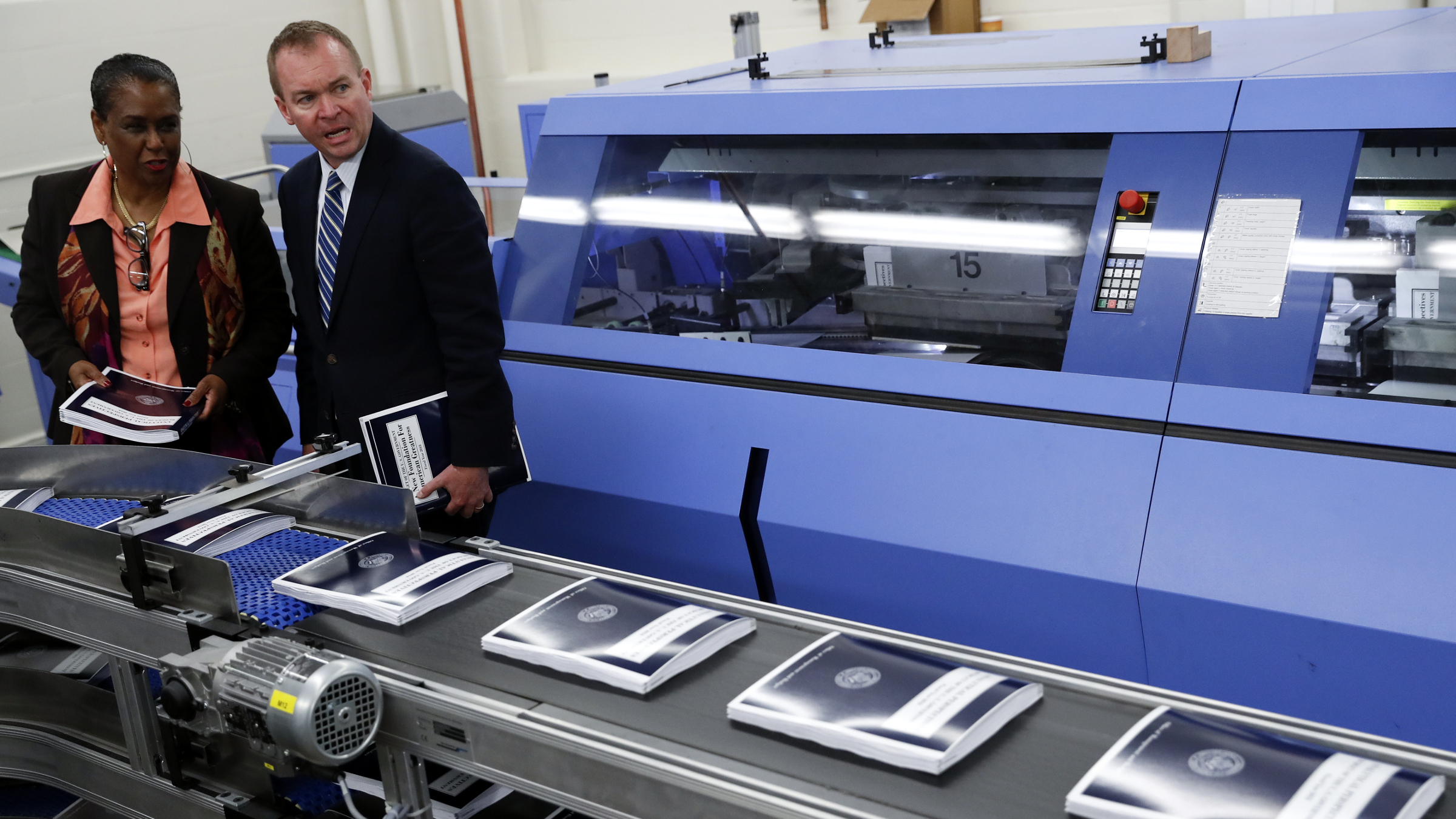 White House budget director Mick Mulvaney, right, joined by GPO Director Davita Vance-Cooks, inspects the production run of President Donald Trump's fiscal 2018 federal budget, Friday, May 19, 2017, at the U.S. Government Publishing Office's (GPO) plant Washington.
