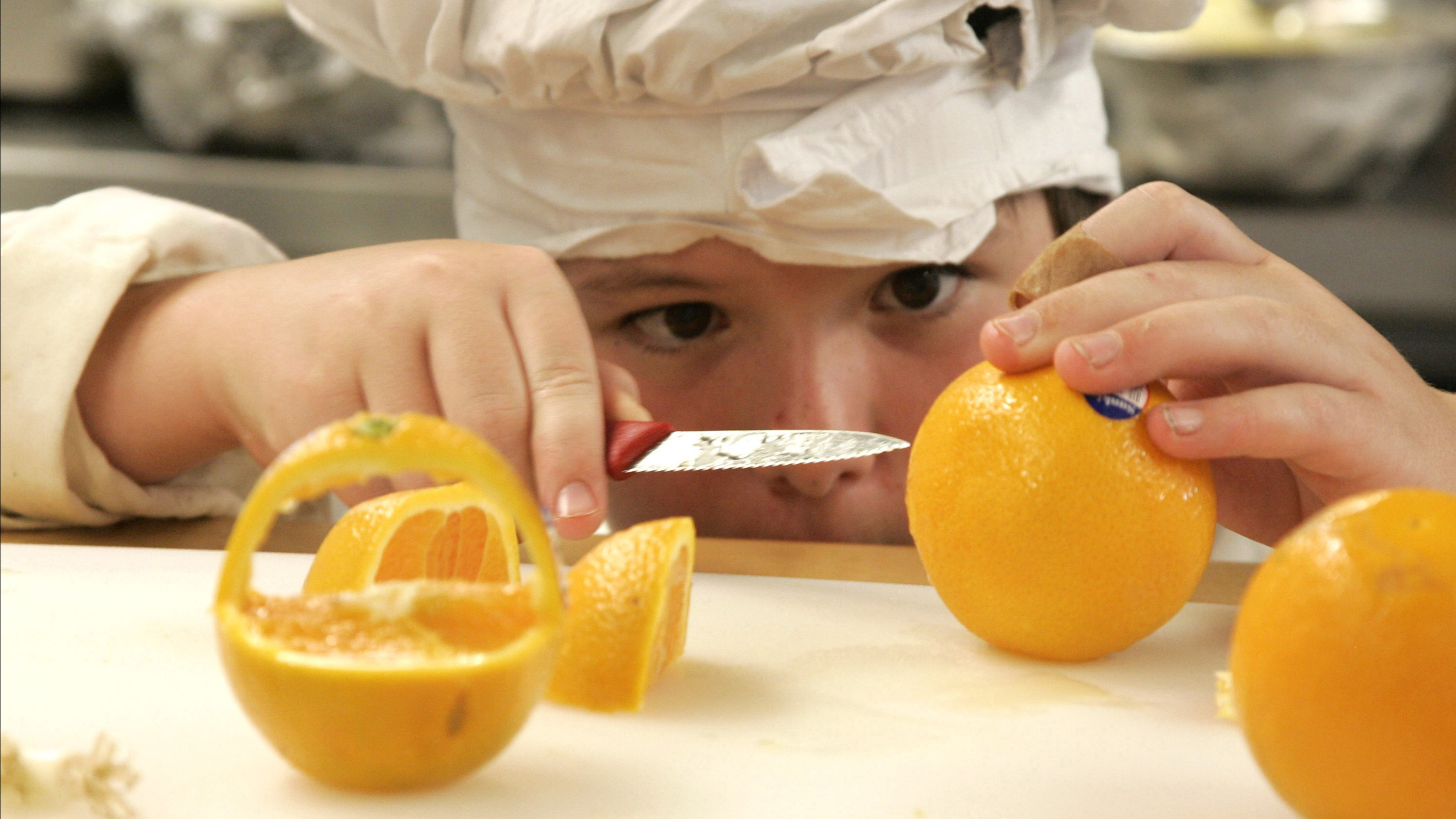 Zeke Andreassen, 11, cuts an orange into a decorative basket  in the kitchen of the Vermont Kids Culinary Academy during a residential cooking summer camp in Highgate, Vermont June 19, 2012. From high-wire walking to plankton propagation to posture lessons, summer camps †are offering an increasingly diverse range of activities compared to the canoe †trips, swim lessons and marshmallow-roasting of yore. The popularity of †alternative camps is helping fuel growth amongst the estimated 12,000 summer †camps in the United States. Despite the stagnant economy, revenues at day camps †grew by 23 percent between 2008 and last year and by 7 percent at sleepaway †camps, according to the American Camp Association, which says the 2,400 organized camps it accredits have combined annual revenues of $2.8 †billion. Picture taken June 19, 2012. To match Feature USA-CAMP/ REUTERS/Herb Swanson (UNITED STATES - Tags: FOOD SOCIETY TPX IMAGES OF THE DAY) - RTR346RA