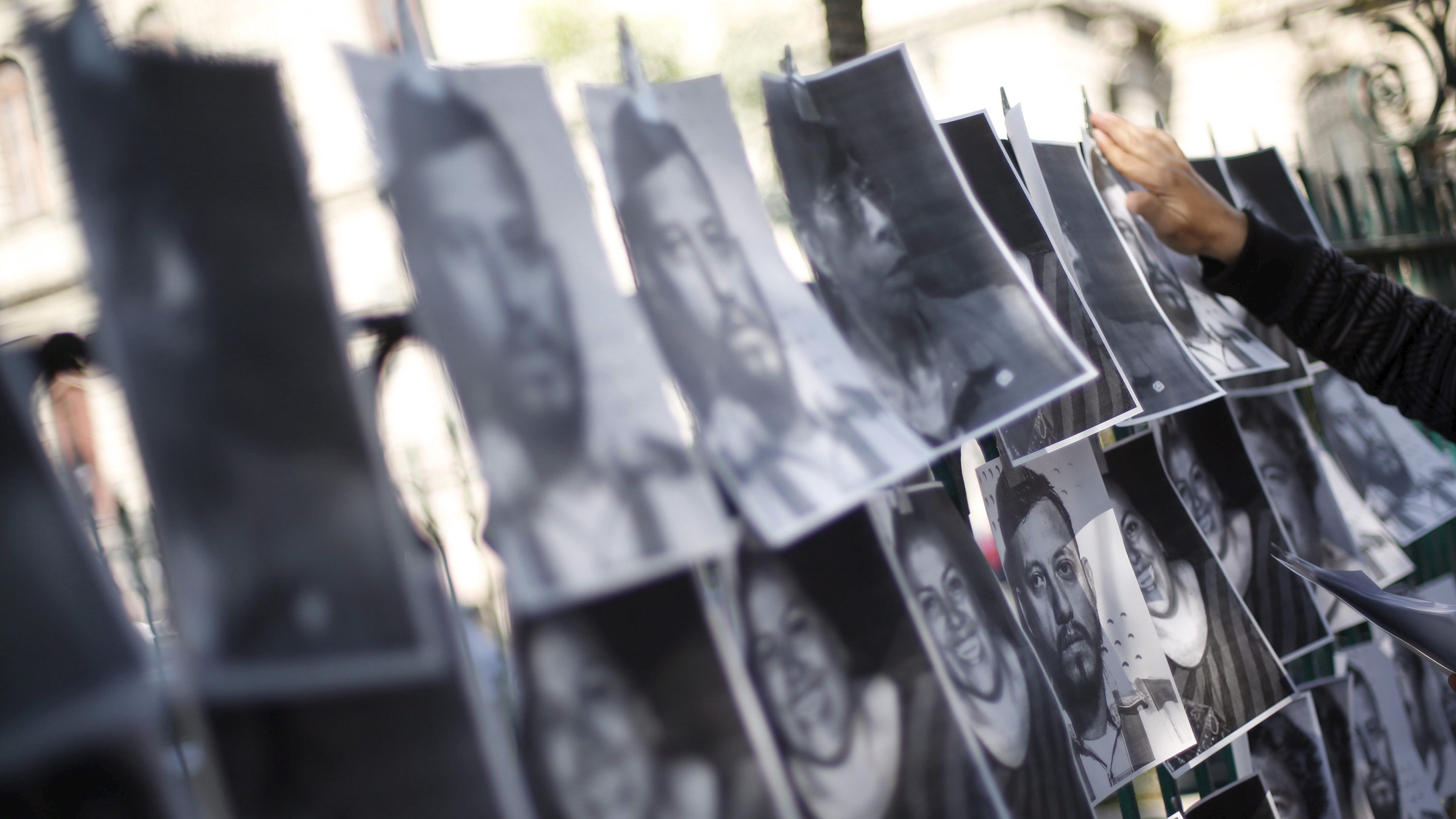 A man hangs images of murdered journalists during a demonstration