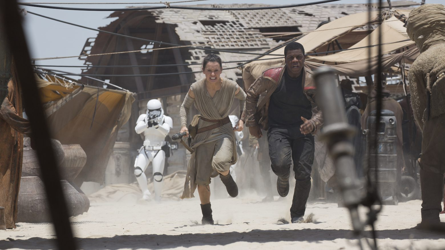 Rey and Finn from Star Wars run from a Stormtrooper