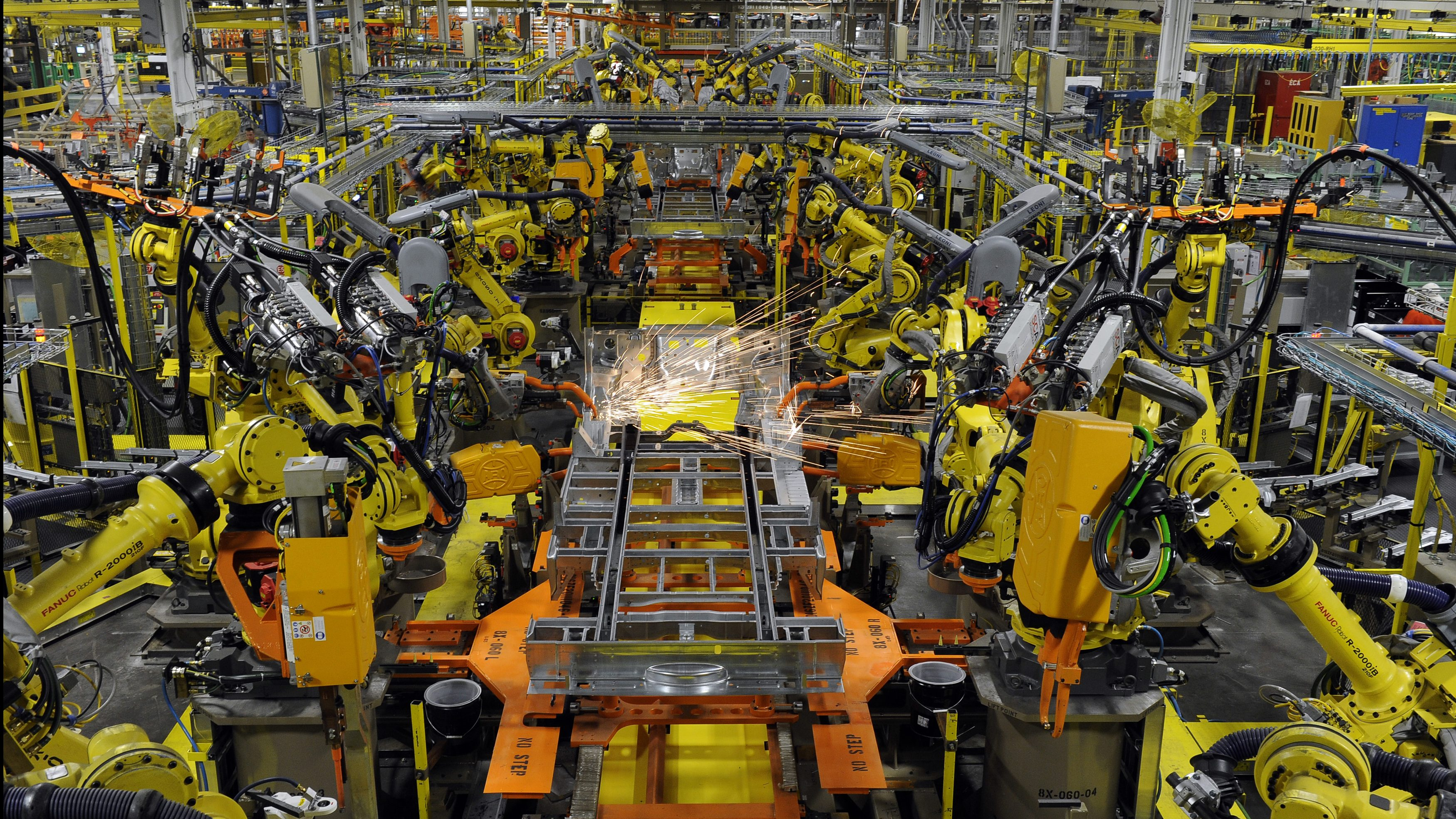 Robotic arms spot welds on the chassis of a Ford Transit Van
