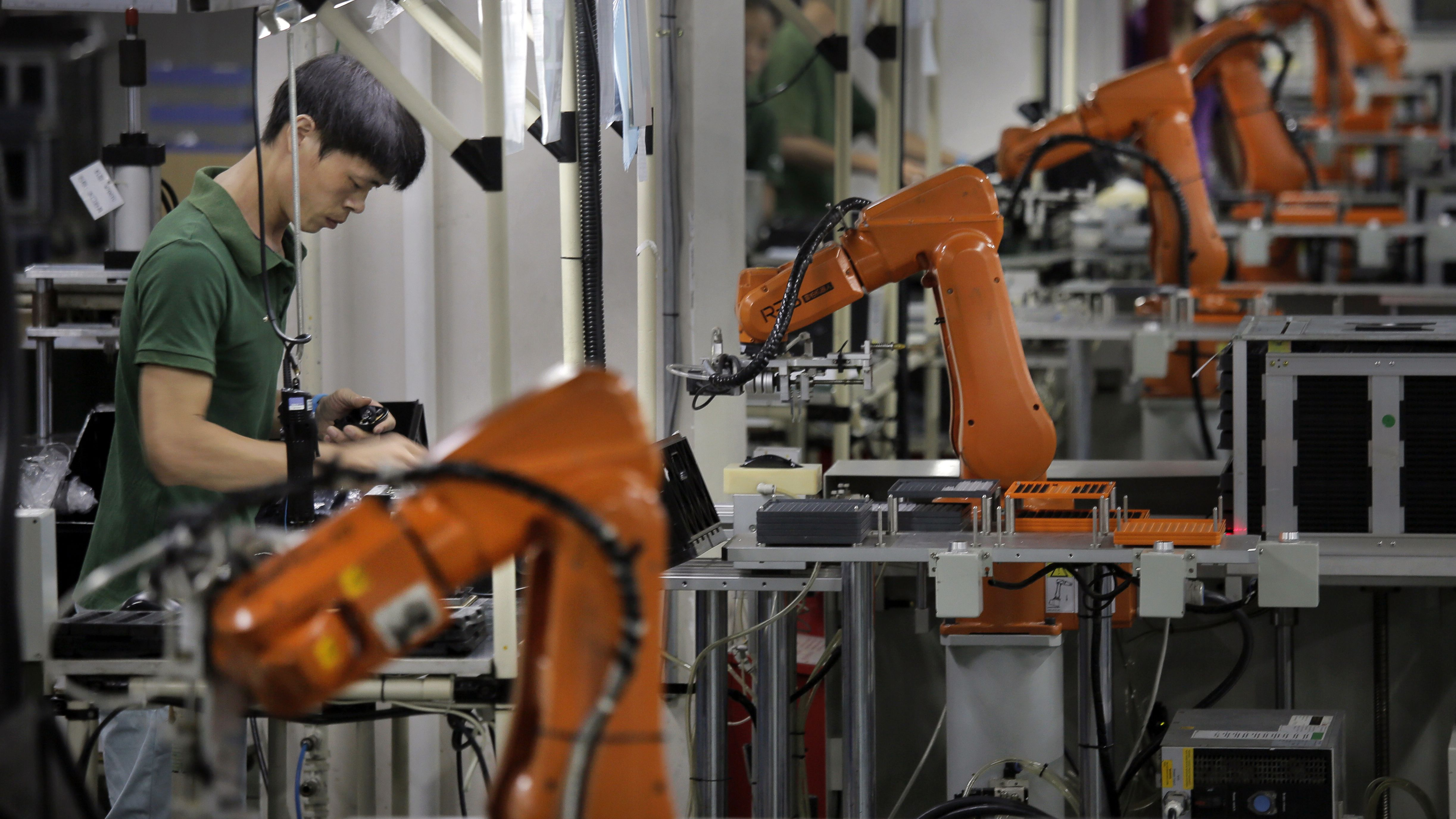 In this Aug. 21, 2015 photo, a Chinese man works next to some orange robot arms at Rapoo Technology factory in southern Chinese industrial boomtown of Shenzhen. Factories in China are rapidly replacing those workers with automation, a pivot that's encouraged by rising wages and new official directives aimed at helping the country move away from low-cost manufacturing as the supply of young, pliant workers shrinks. (AP Photo/Vincent Yu)