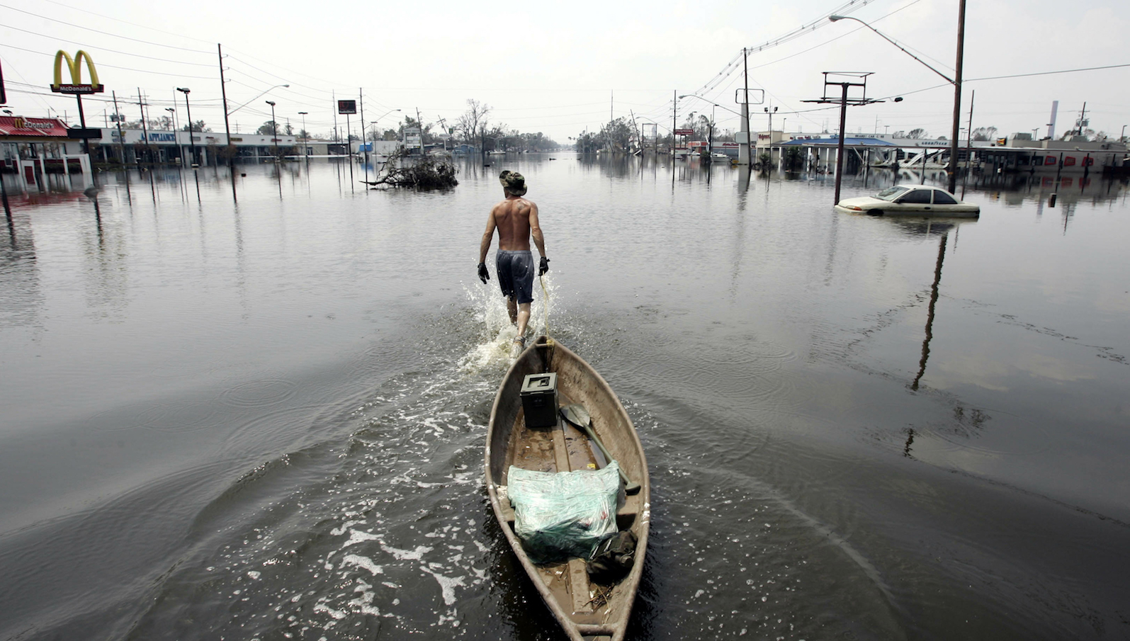 Hurricane Katrina survivor Paul Metzler pulls his boat along Paris St in Chalmette, a community about 7 miles (11 km) east of New Orleans, September 3, 2005. For the first time since Hurricane Katrina struck on August 29, rescuers are scouring the community for survivors. REUTERS/Jason Reed   also see GF2DVFMXNPAA - RTR18QSN