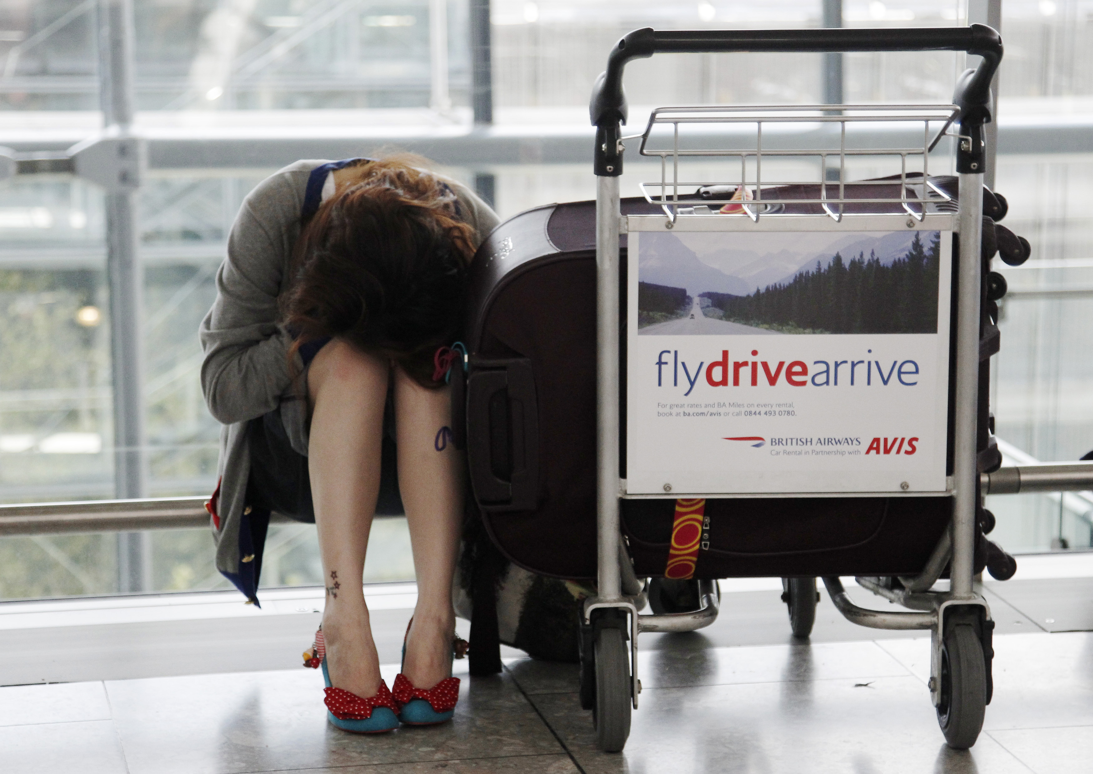 A travellers rest with her luggage as flights are delayed and cancelled at Heathrow Airport in London