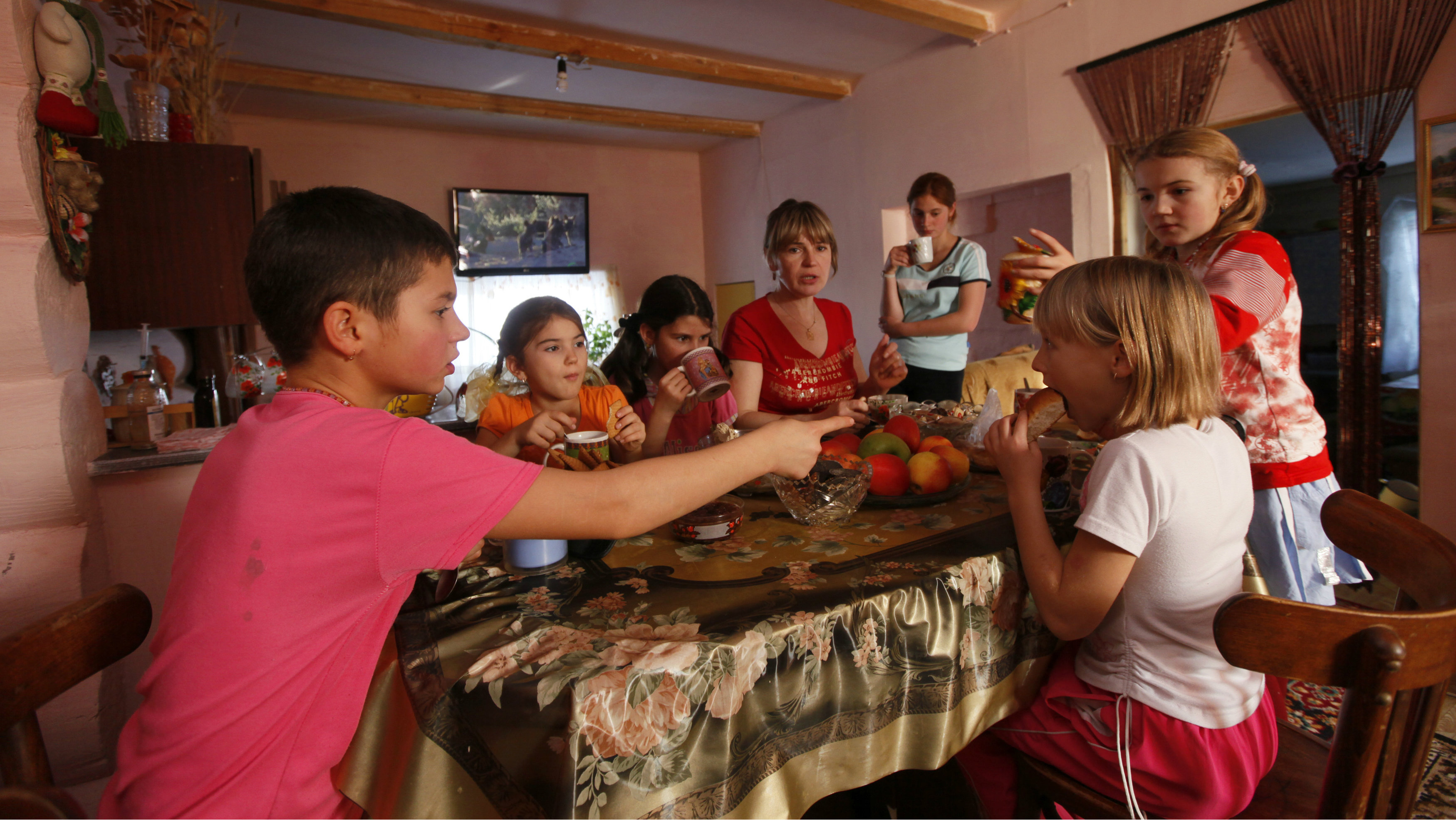 Zoya Lipnyagova and her children have dinner at their farmhouse in the village of Kluchi