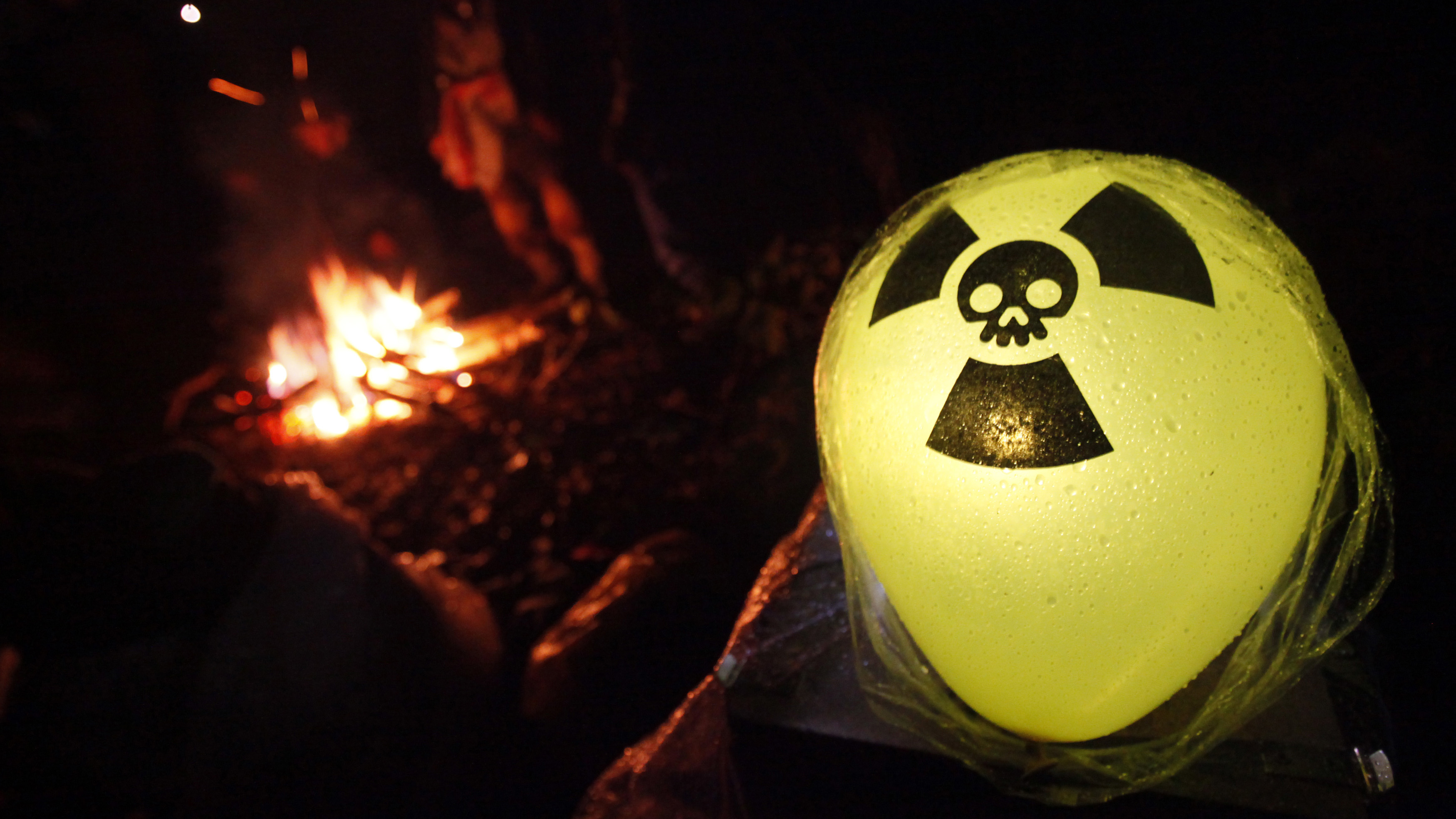An illuminated balloon with the nuclear symbol is seen as anti-nuclear protesters warm themselves around a camp fire during a sit-in of hundreds of demonstrators on the rails near Harlingen November 26, 2011, to block a train carrying nuclear waste. The Castor (Cask for Storage and Transport Of Radioactive material) train is carrying 11 containers of spent German nuclear fuel on route from France after being reprocessed, to the nuclear waste storage facility of Gorleben in north eastern Germany this weekend. REUTERS/Wolfgang Rattay   GERMANY (ENVIRONMENT POLITICS CIVIL UNREST) - RTR2UI6O