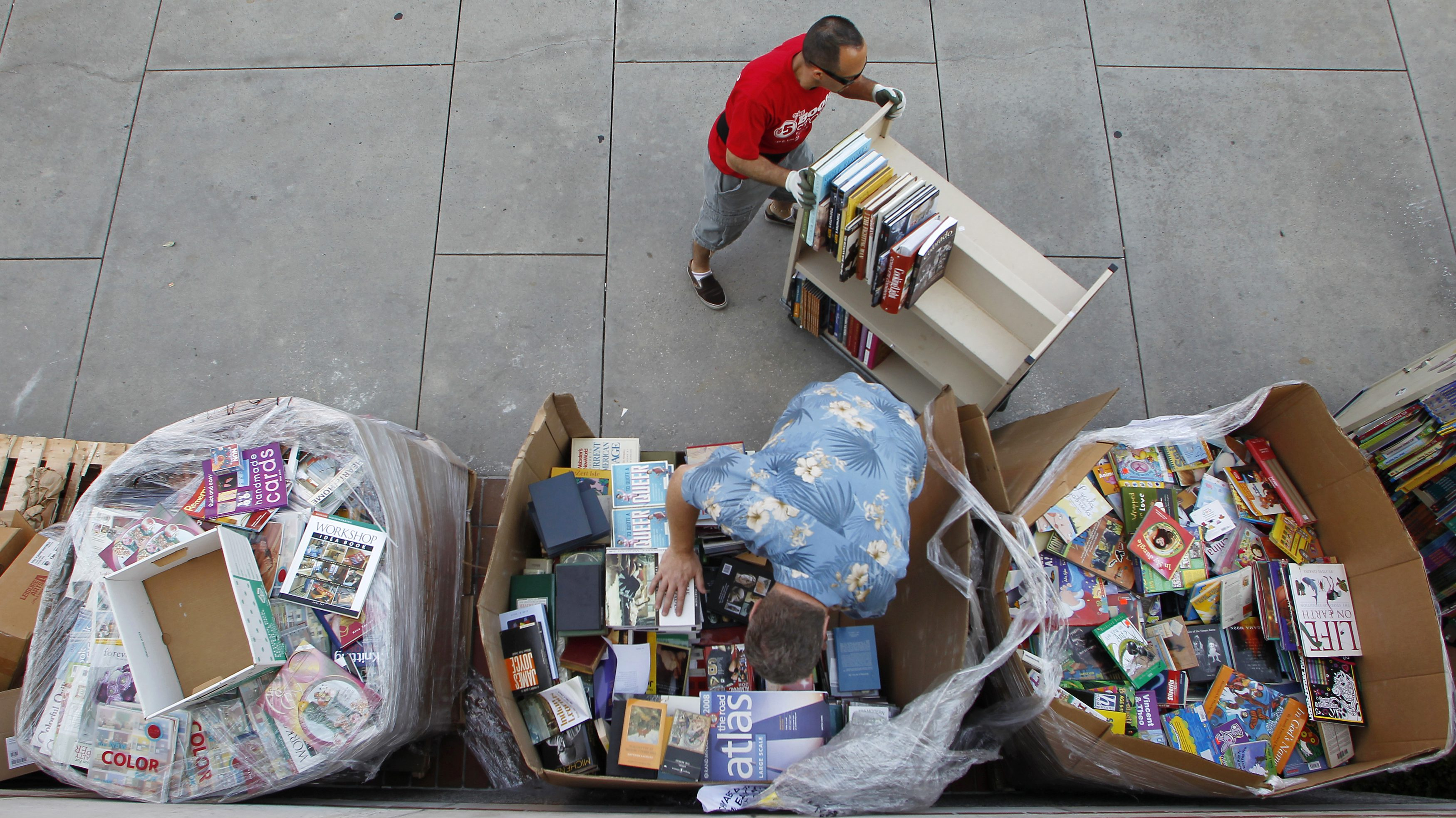 """Serapin De La Torre (top) and Greg Schwabe (bottom) load books from pallets onto a cart to re-stock shelves at the """"$5.00 or less BOOKSTORE"""" booth at the Los Angeles Times Festival of Books on the campus of the University of Southern California in Los Angeles April 21, 2012. REUTERS/Danny Moloshok (UNITED STATES - Tags: SOCIETY MEDIA) - RTR311KZ"""