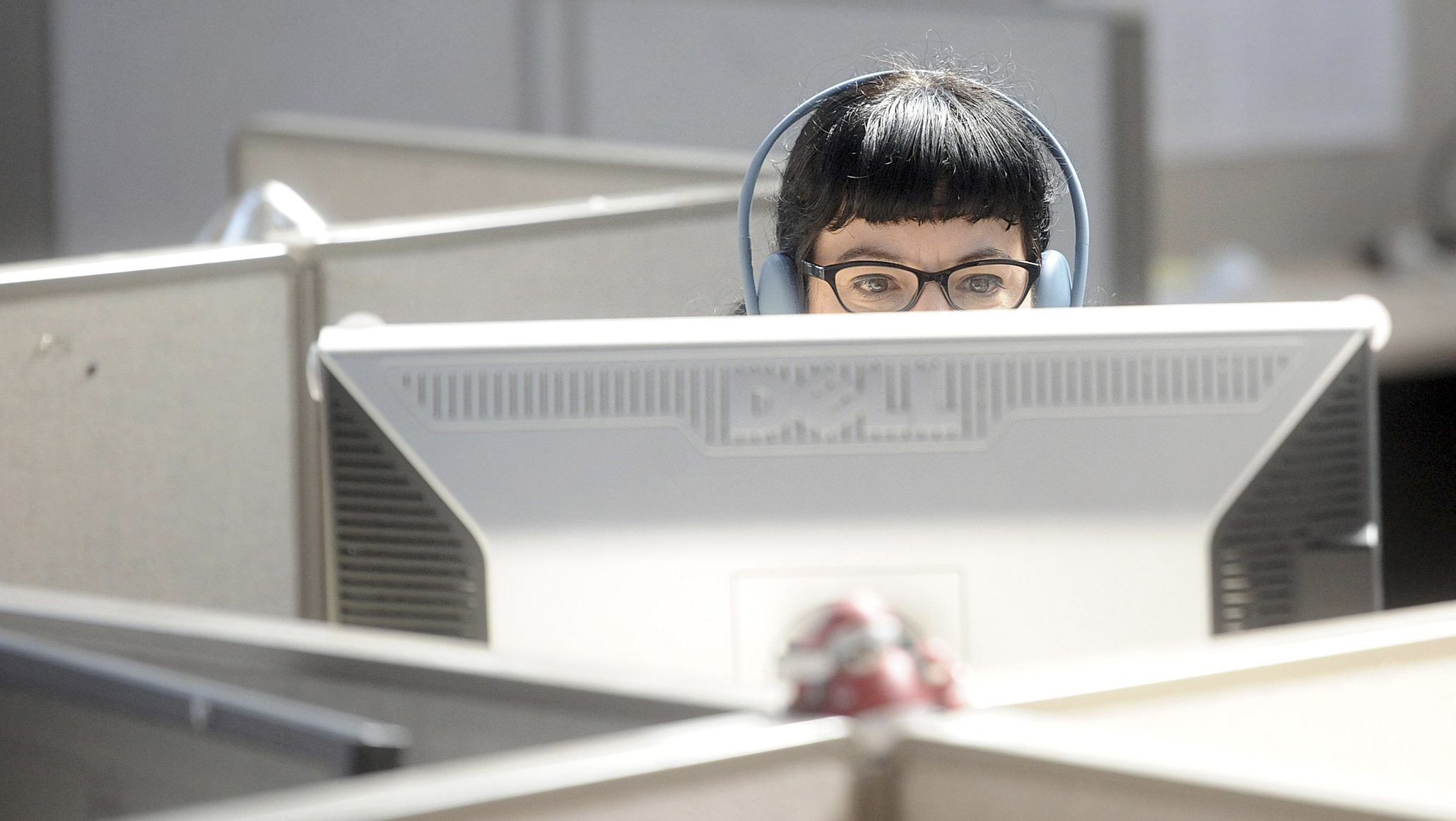 A woman is at her desk partially hidden behind her monitor