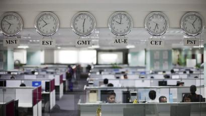 Workers are pictured beneath clocks displaying time zones in various parts of the world at an outsourcing centre in Bangalore February 29, 2012.