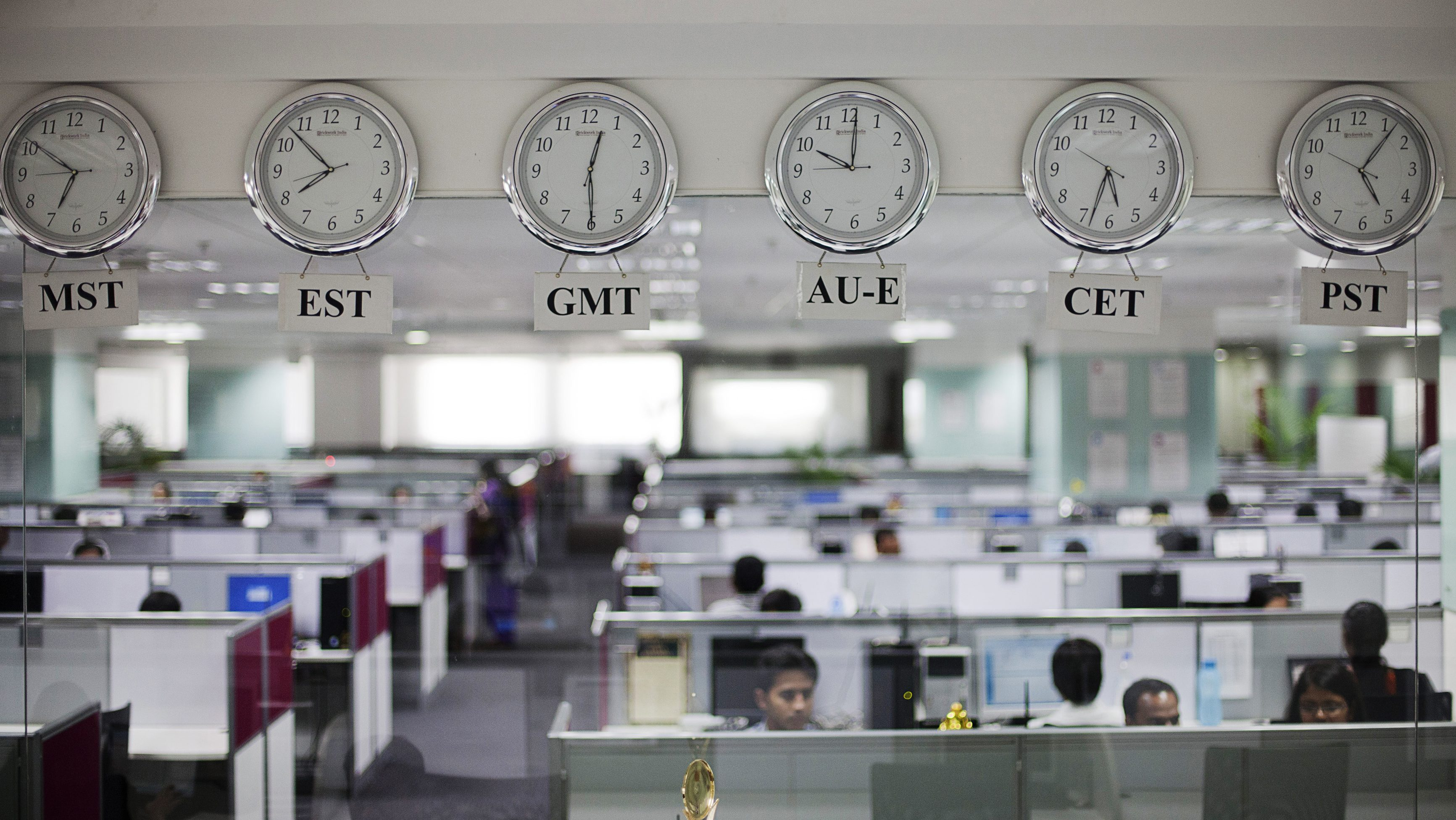 Workers are pictured beneath clocks displaying time zones in various parts of the world at an outsourcing centre in Bangalore February 29, 2012. The business of storing, decoding and analysing unstructured data - think video, Facebook updates, Tweets, Internet searches and public cameras - along with mountains of facts and figures can help companies increase profits, cut costs and improve service, and is now one of the world's hottest industries. It's called Big Data, and although much of the work is done in the United States, India is getting an increasing slice of the action, re-energising an IT sector whose growth has begun to falter. Picture taken February 29, 2012.