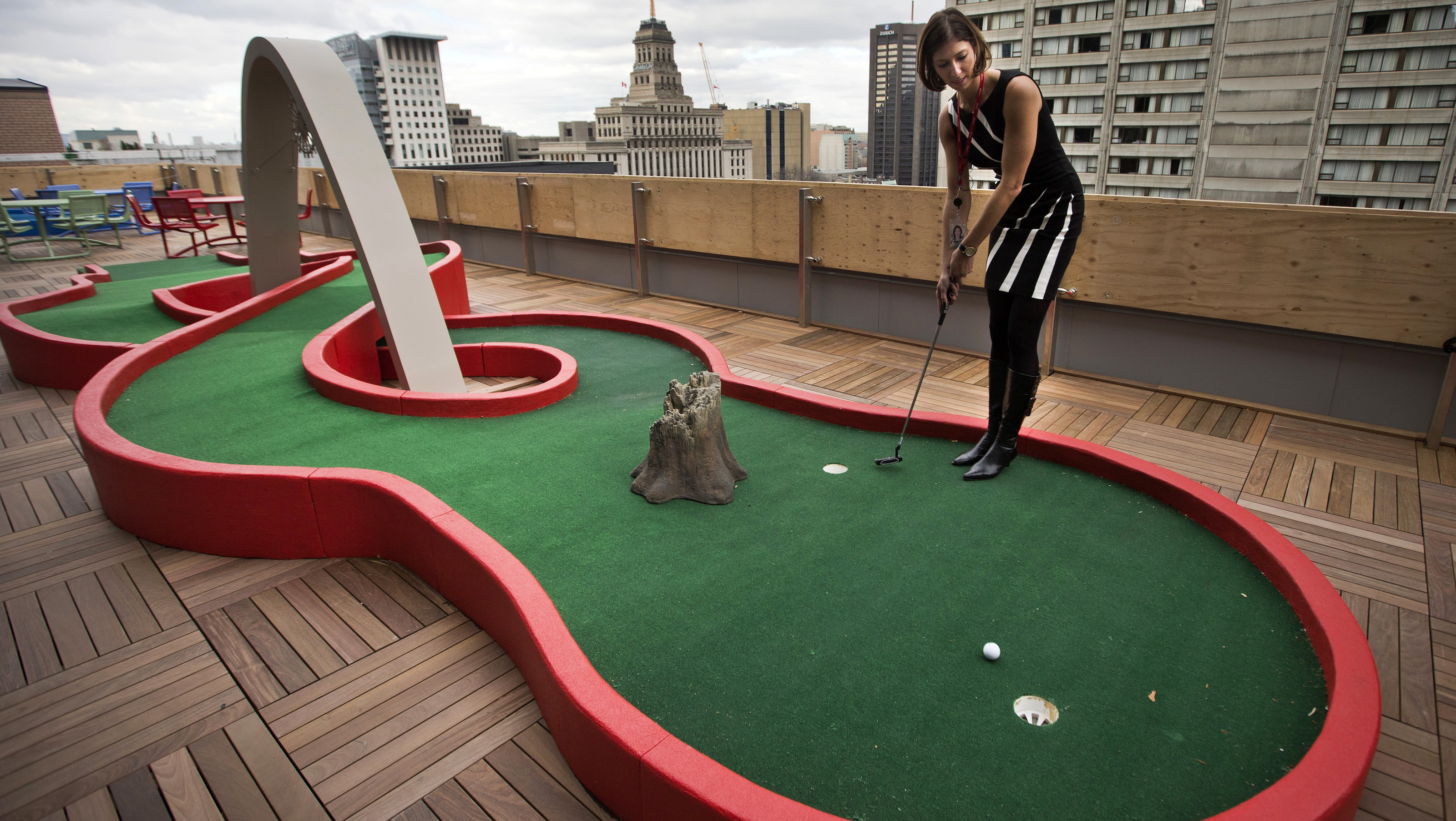 Google employee Andrea Janus demonstrates the use of the mini-putt green on the balcony at the new Google office in Toronto, November 13, 2012.    REUTERS/Mark Blinch (CANADA - Tags: SCIENCE TECHNOLOGY BUSINESS) - RTR3AD00