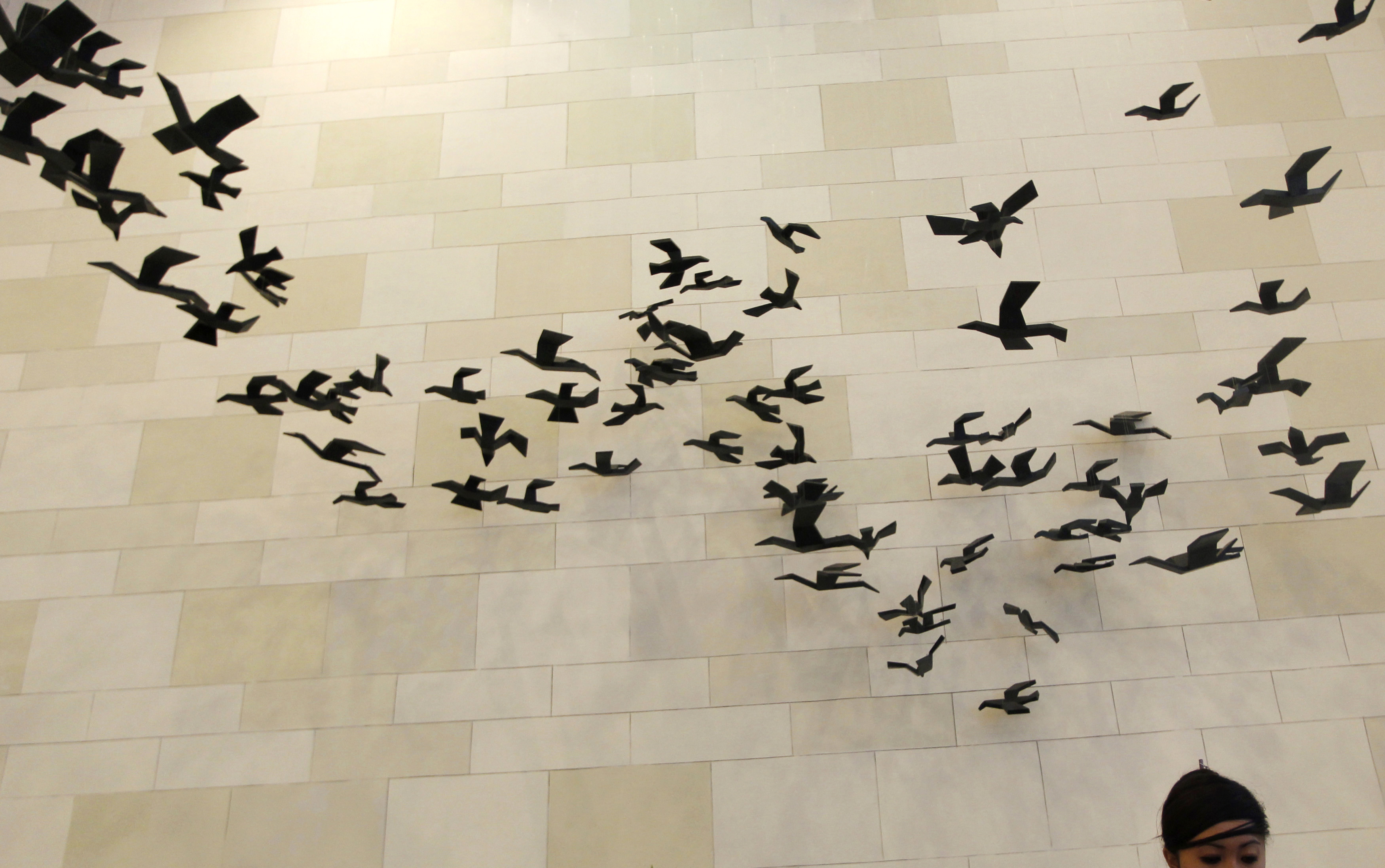 An art installation of suspended doves hangs above a receptionist at the media center of the Asia-Pacific Economic Cooperation (APEC) forum in Nusa Dua, Bali, October 5, 2013. REUTERS/Edgar Su (INDONESIA - Tags: SOCIETY MEDIA POLITICS BUSINESS) - RTR3FM9N