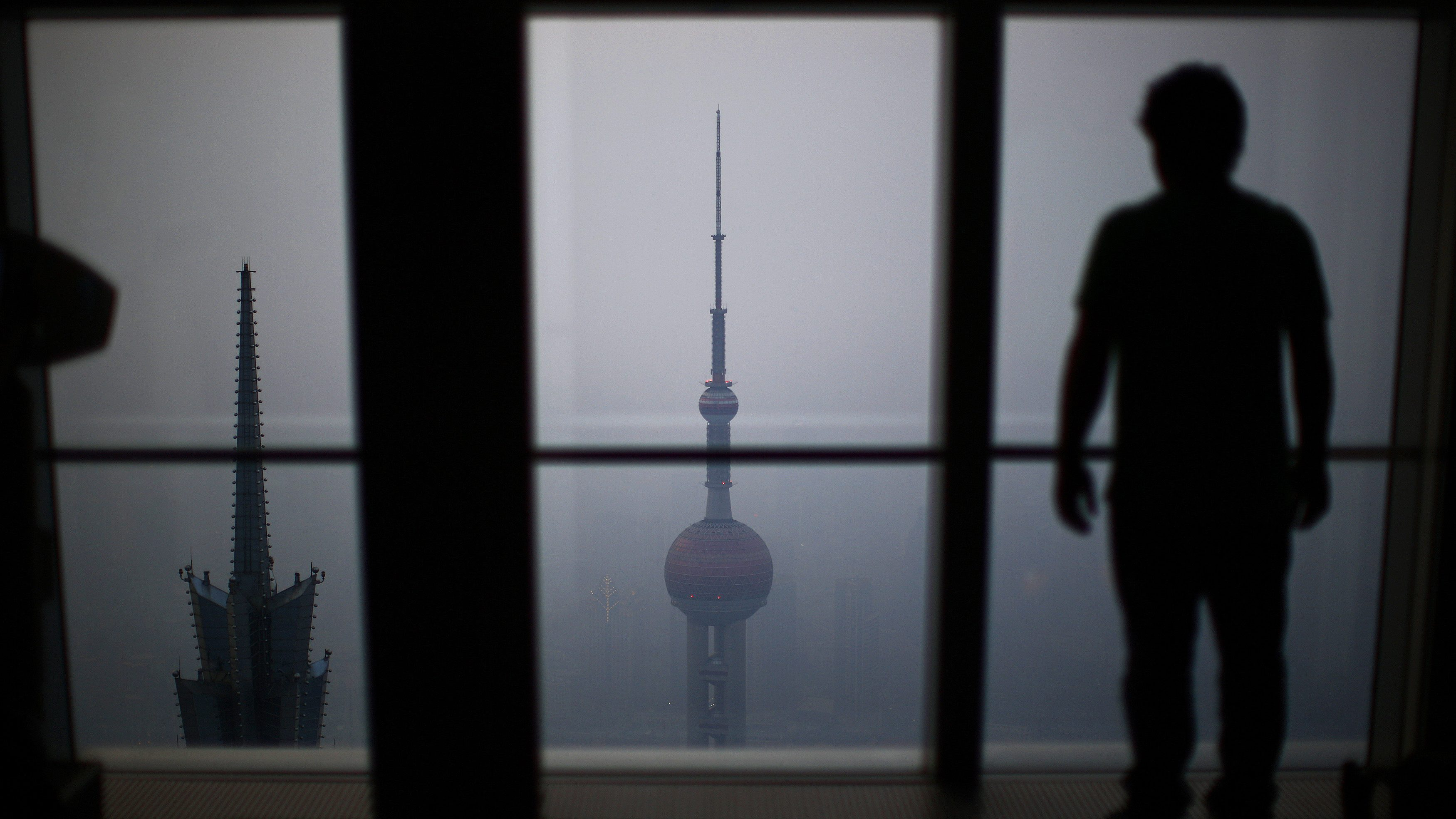 A man looks at the Oriental Pearl TV Tower on a hazy day at Pudong financial district in Shanghai March 18, 2014. China pledged on Sunday that it will make sure that 60 percent of its cities meet national pollution standards by 2020, with pressure growing to make cities liveable as hundreds of millions of migrants are expected to relocate from the countryside.