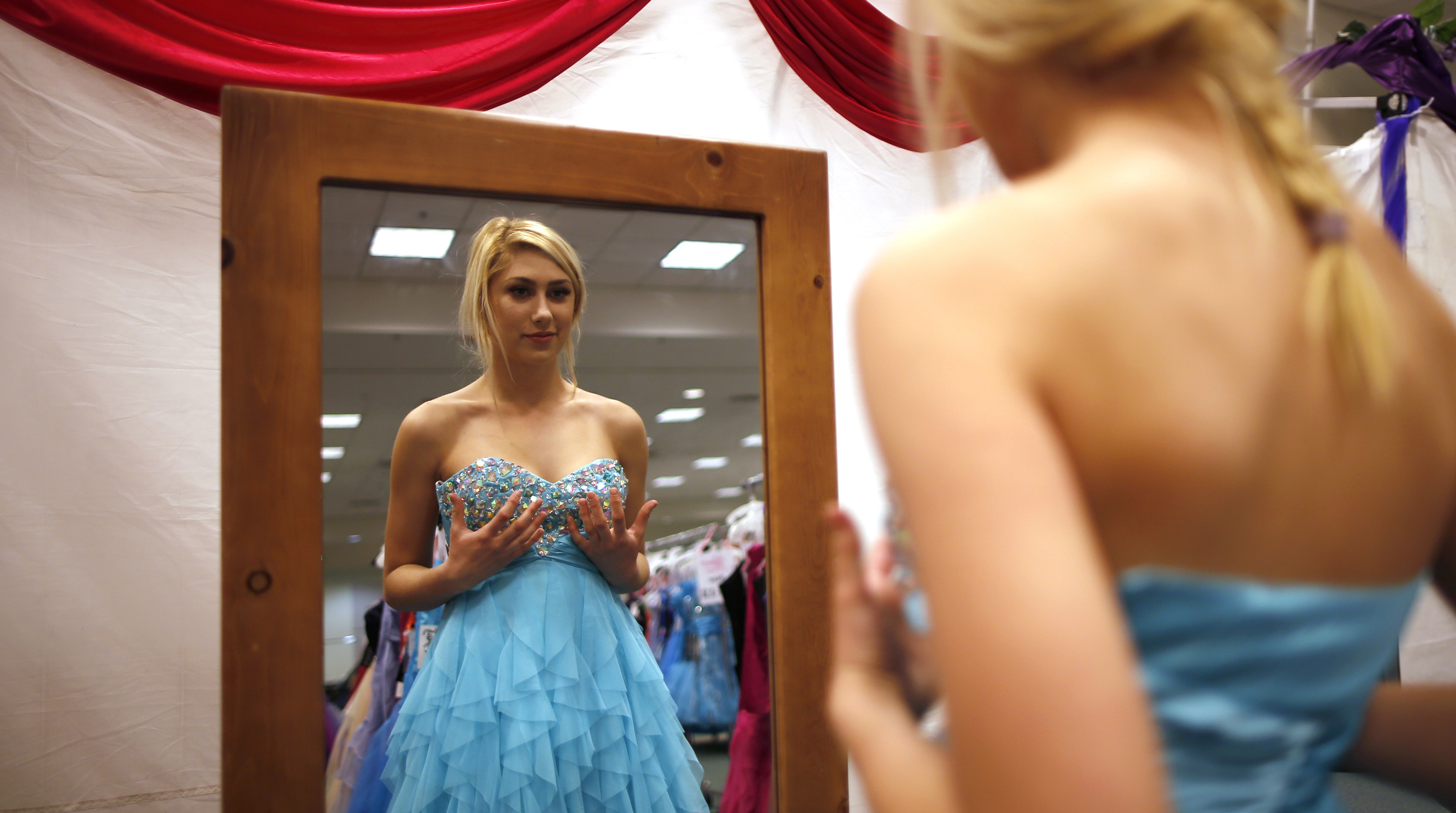 Jasmine Boyle, 17, tries on a prom dress at the Glamour Gowns event in Los Angeles, California March 28, 2014. The event gives prom dresses to more than 350 young women in the Los Angeles foster care system every year. Picture taken March 28, 2014. REUTERS/Lucy Nicholson (UNITED STATES - Tags: SOCIETY) - RTR3J4O3