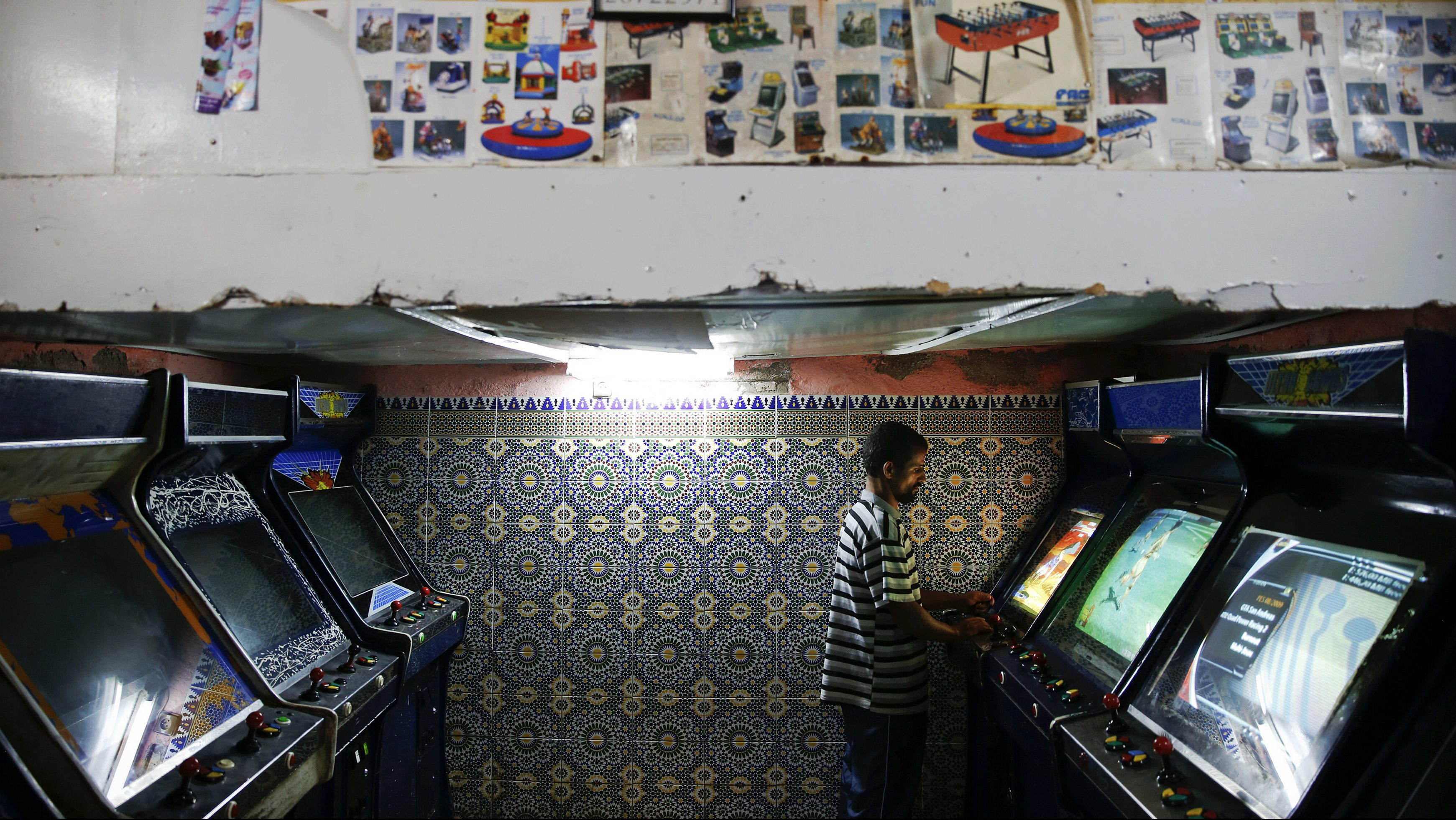 "A man plays video games in an entertainment saloon in Rabat's Medina September 21, 2014. UNESCO made Rabat a World Heritage Site two years ago and media and tour operators call it a ""must-see destination."" But it seems the tourist hordes have yet to find out. While visitors are getting squeezed through the better-known sites of Marrakesh and Fez, the old part of Rabat - with its beautiful Medina and Kasbah of the Udayas - remains an almost unspoiled oasis of calm. Smaller and more compact, its labyrinths of streets, passages and dead ends are a treasure trove of shapes and colours, of moments begging to be caught by the photographer's lens. Picture taken September 21, 2014."